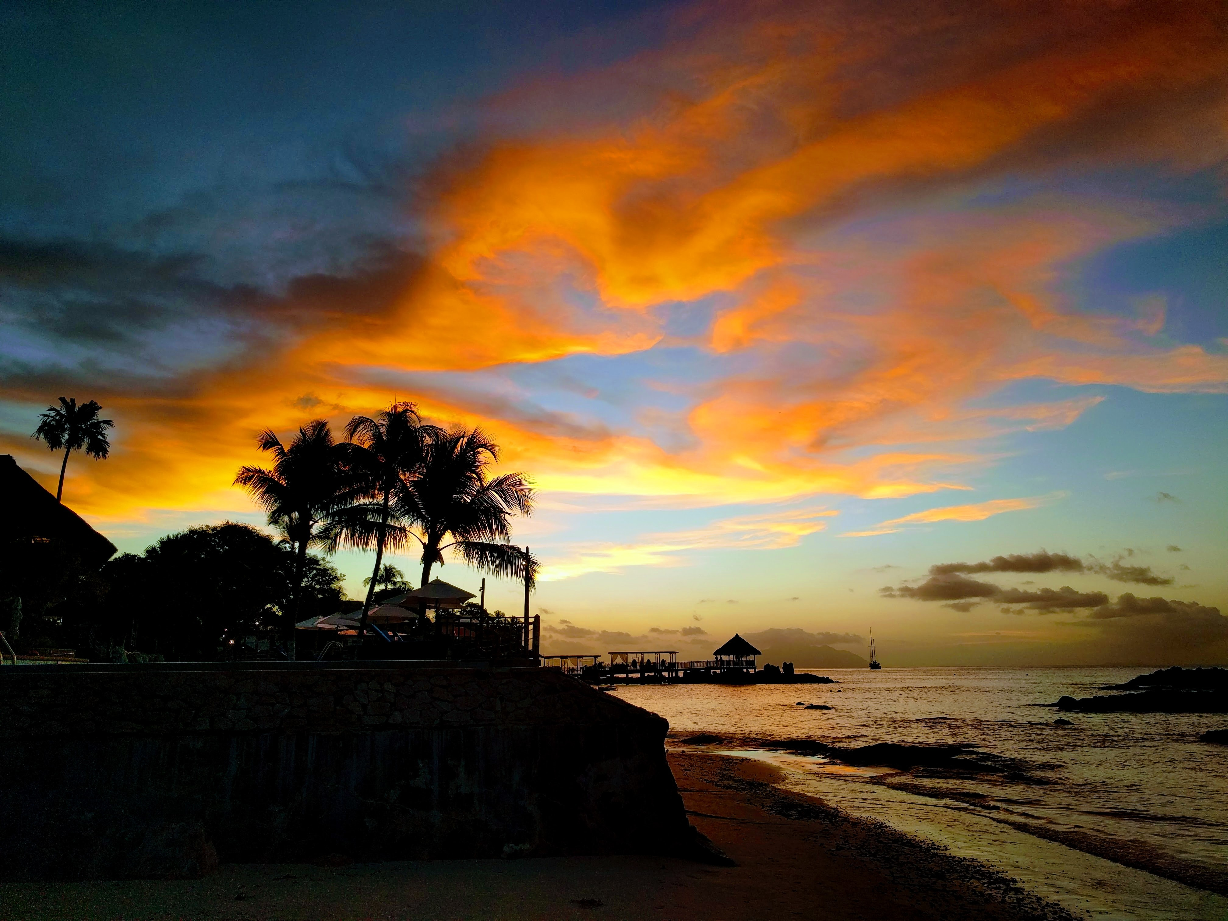 Sunlit clouds during sunset at the Bel Ombre beach, Seychelles