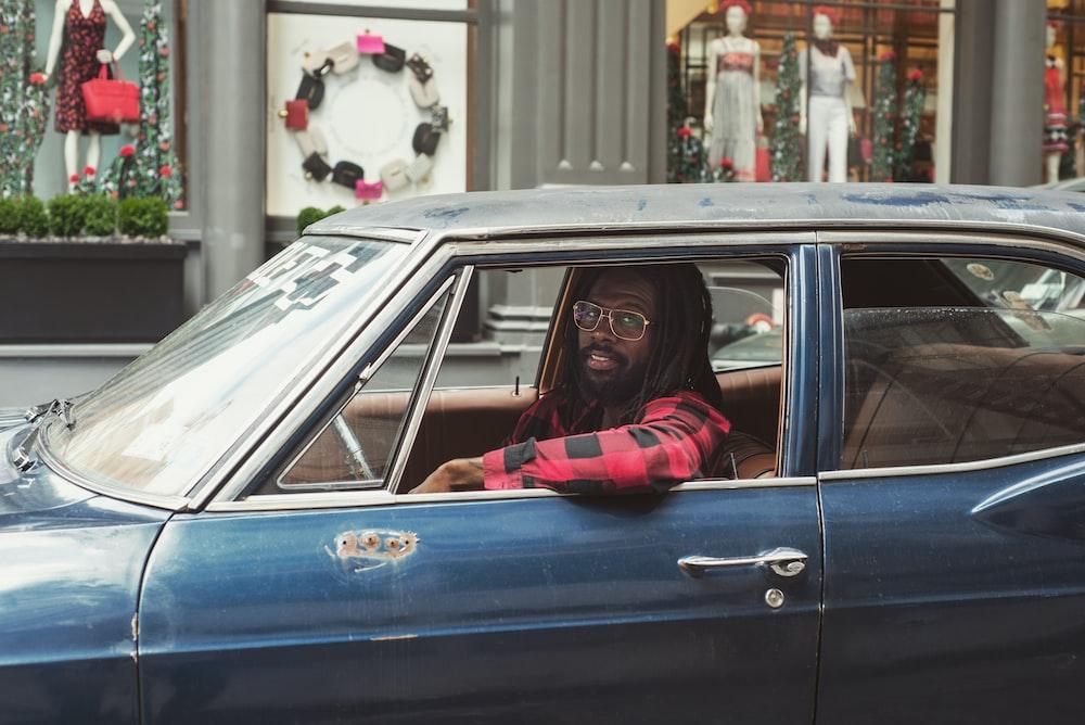 man driving blue car