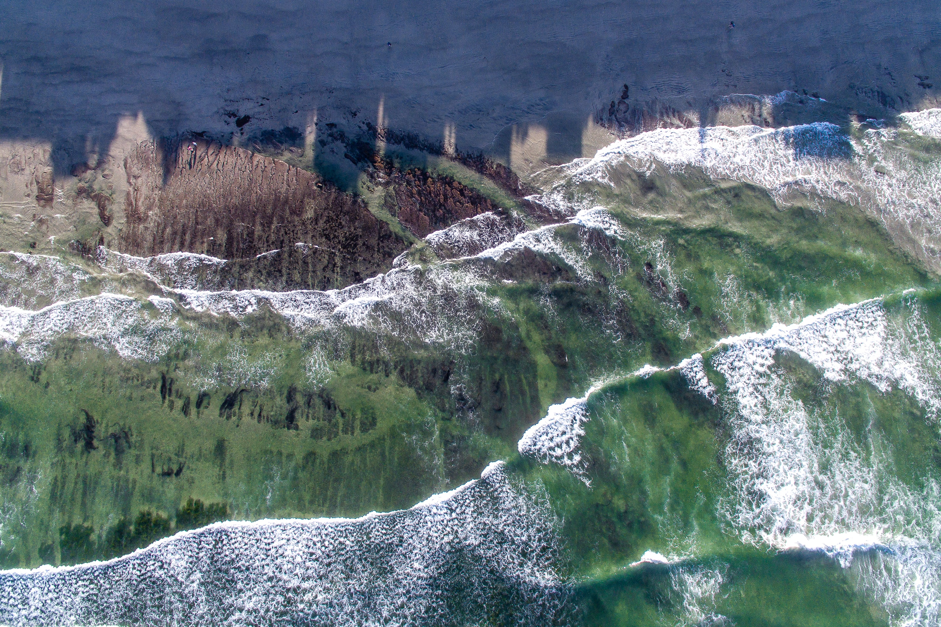 Drone view of ocean waves going across colorful terrain at Beacon's Beach