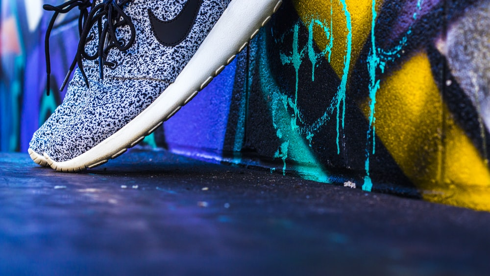 unpaired gray and white Nike sneaker leaning on concrete wall with graffiti