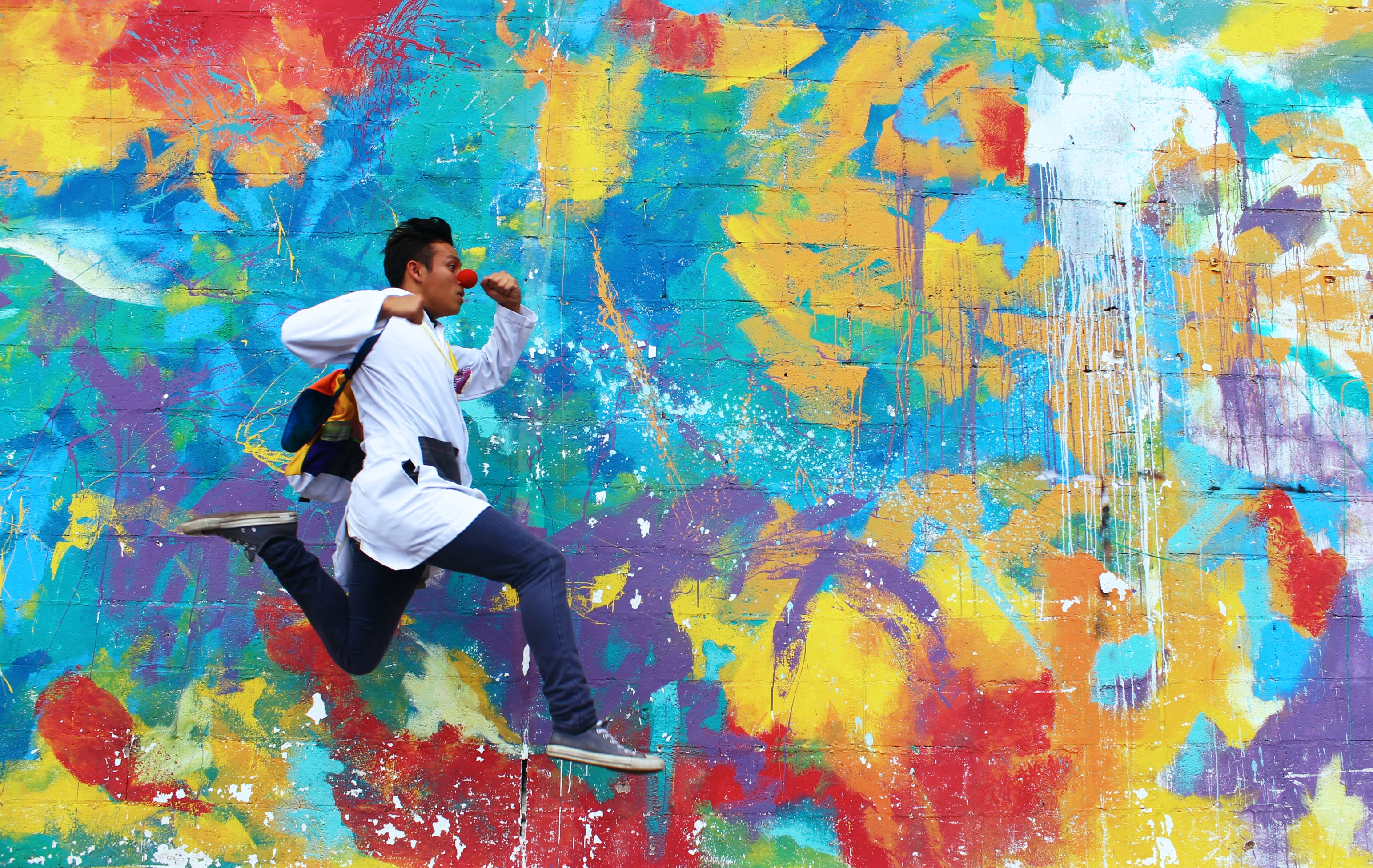 A dark-skinned male leaping along the sidewalk in front of an abstractly painted wall.
