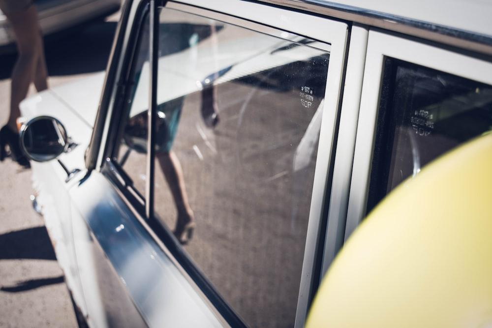 Woman seen walking in the reflection of a car window
