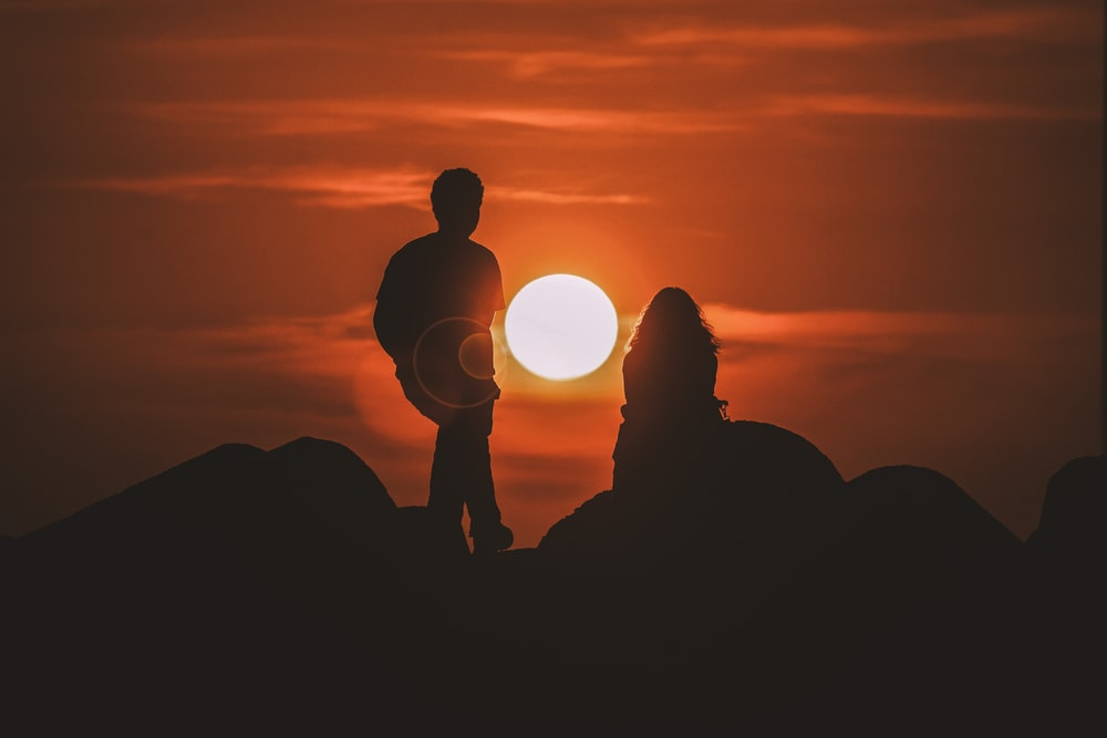 silhouette of two people looking at sunset