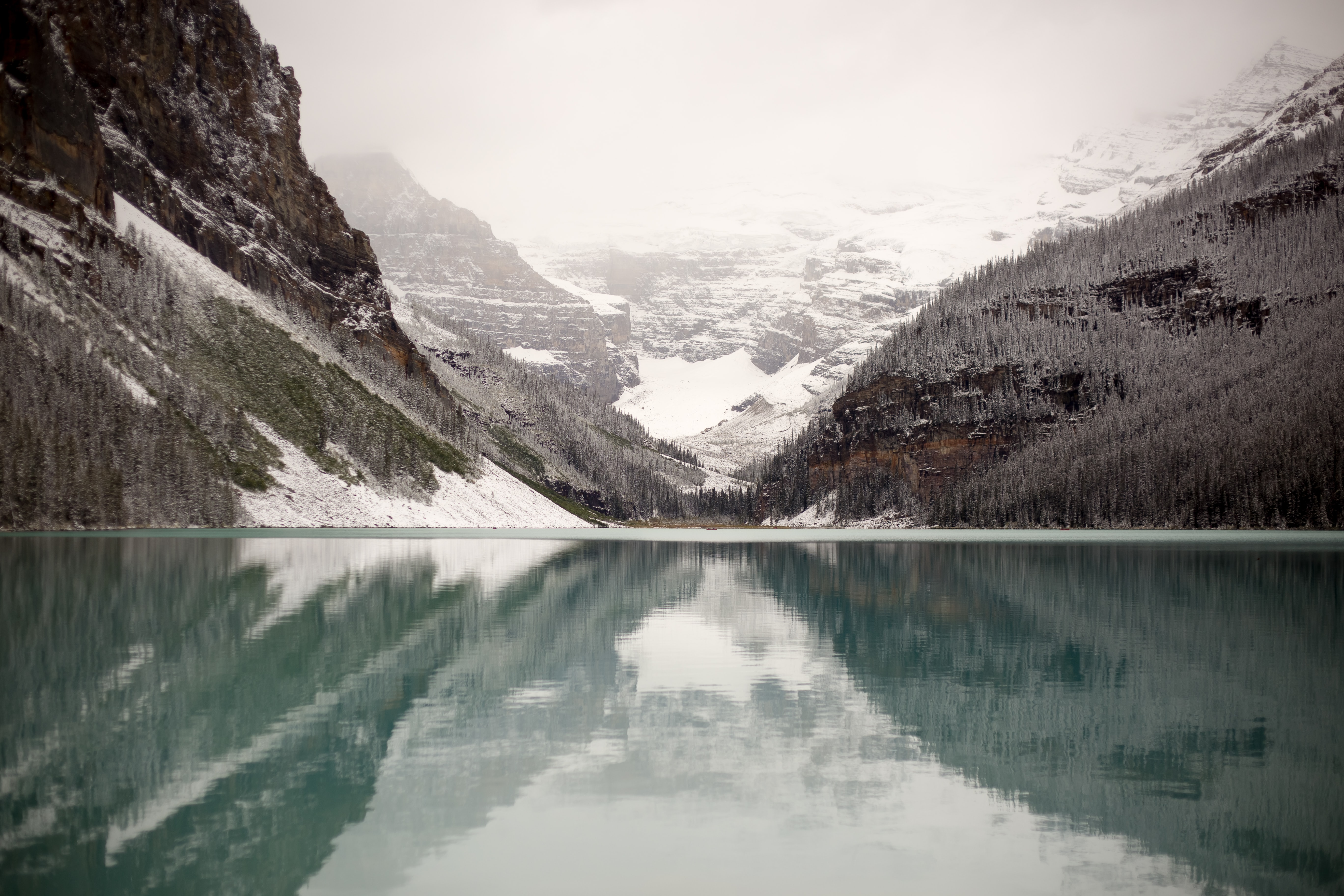 body of water near mountain covered by snow at daytime