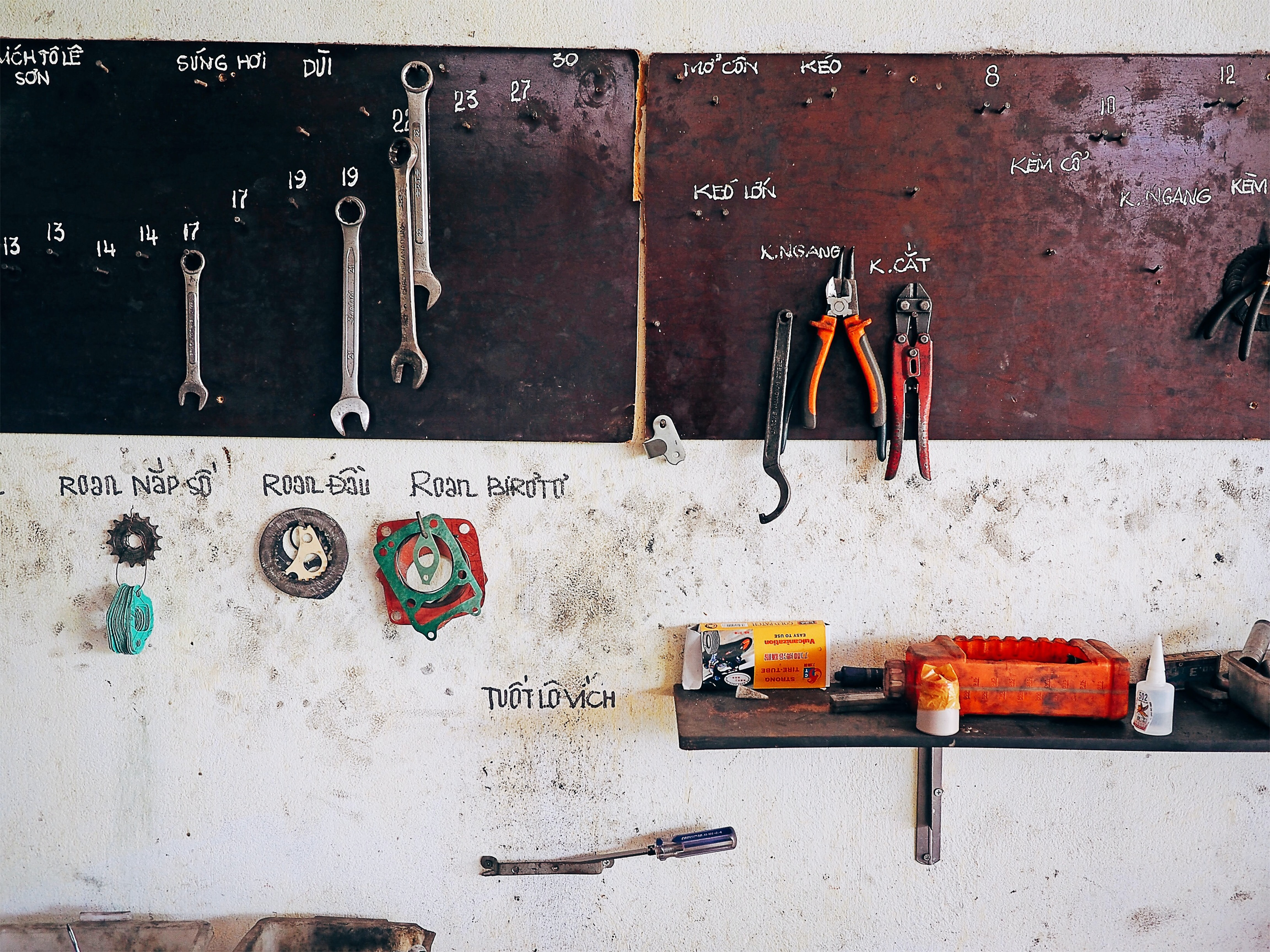 assorted steel tools on brown wall