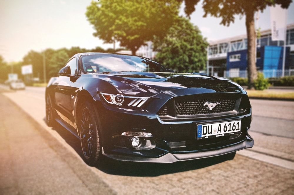 shallow focus photography black Mustang sports car parked beside the street