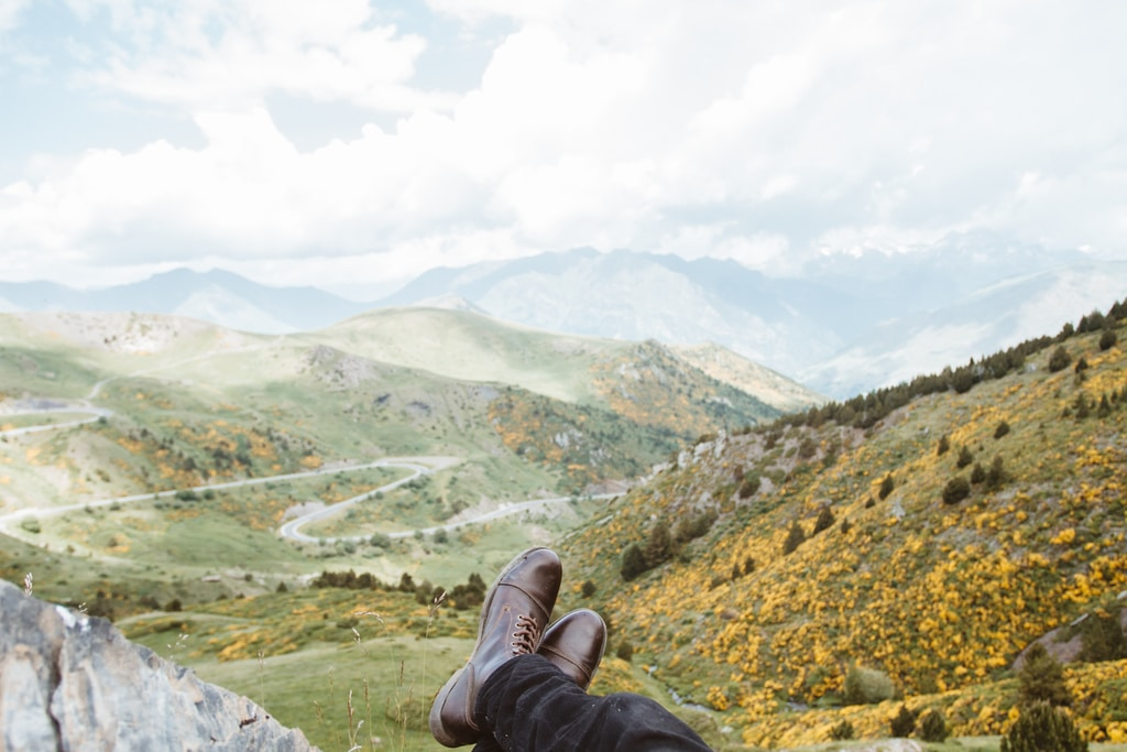 person wearing brown leather boots near mountains at daytime