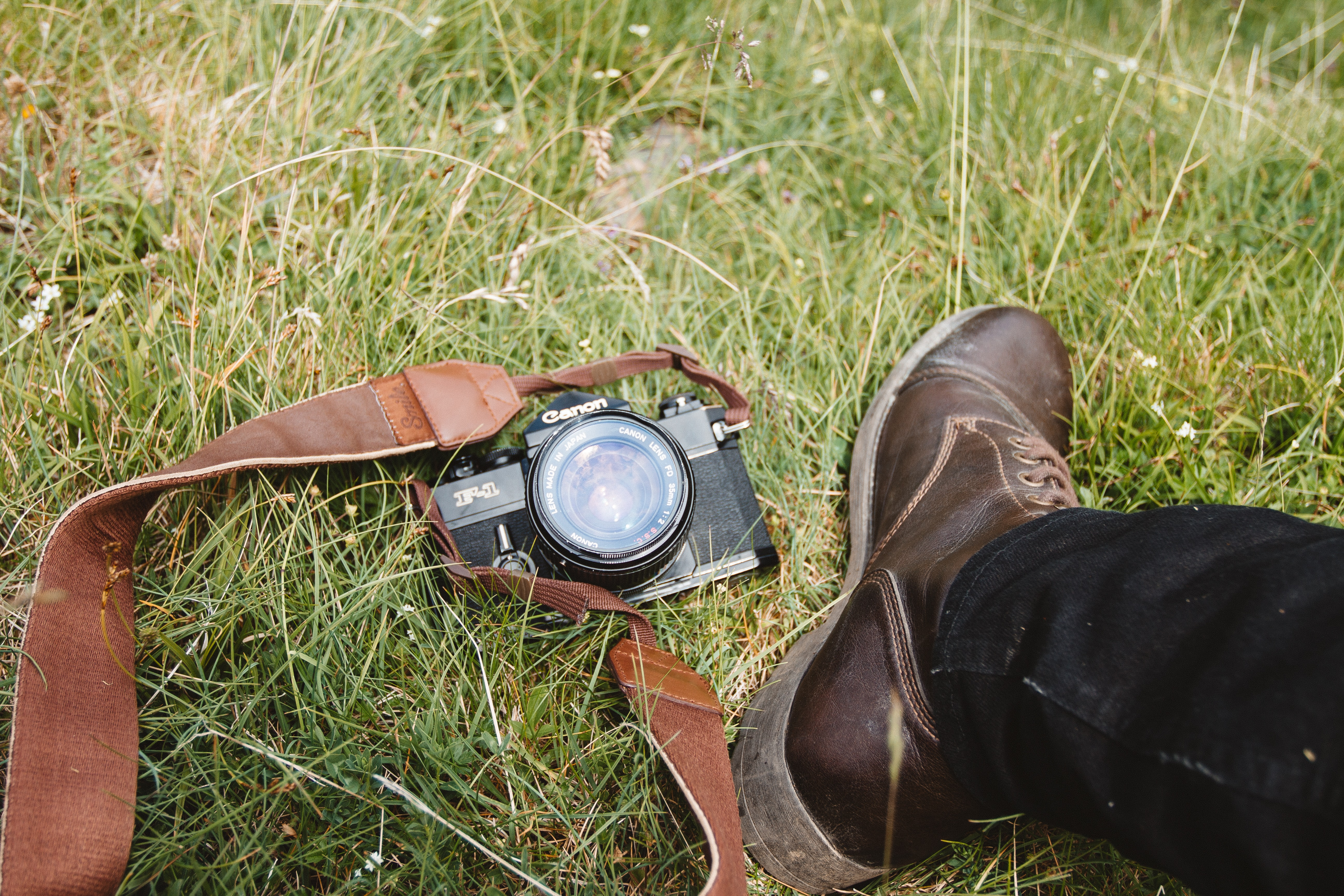 Black Canon F-1 camera with a red strap beside man wearing black pants and a leather boot on a grassy area