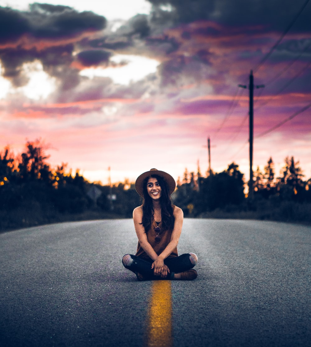 man sitting on concrete road