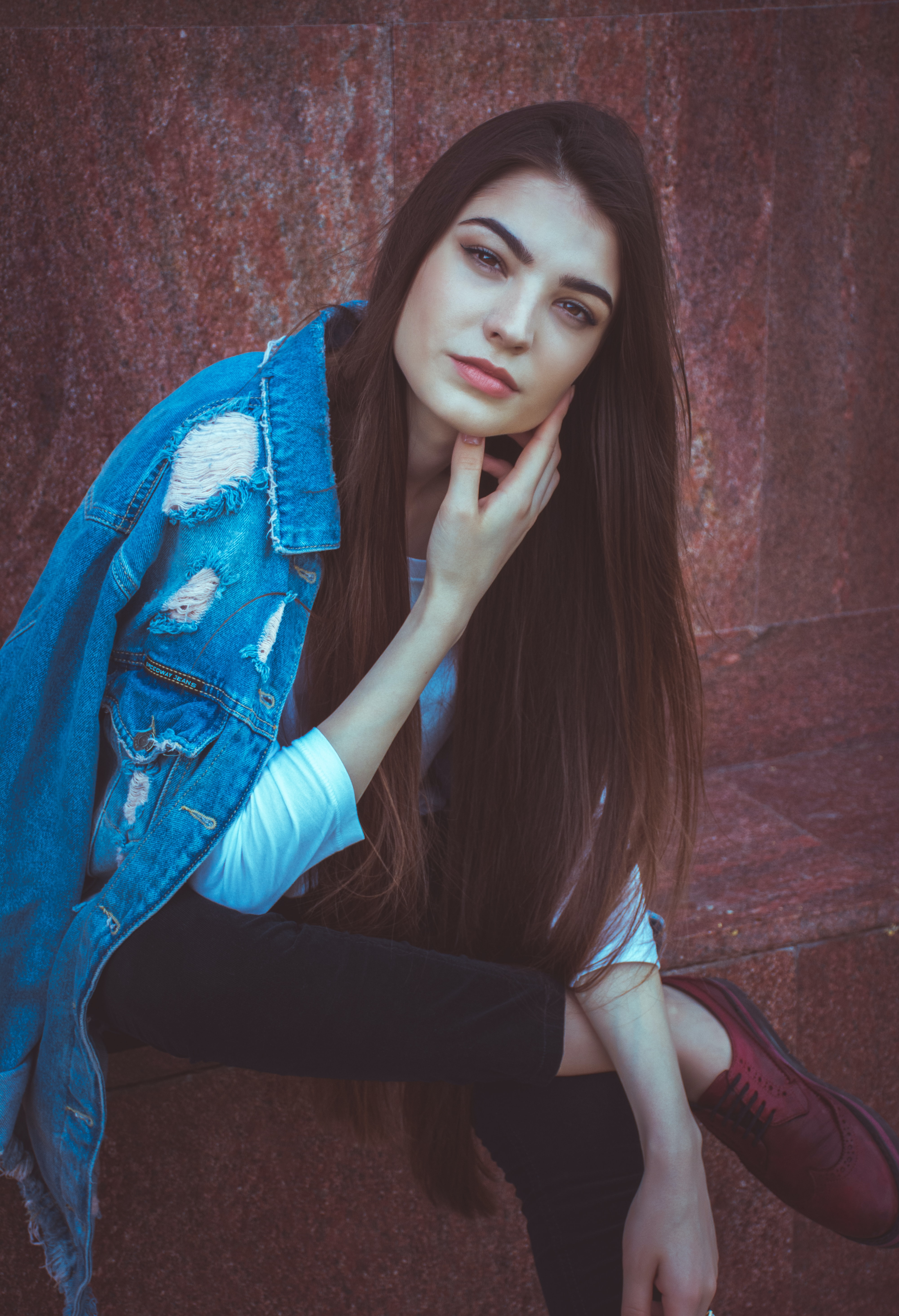 Woman with long hair posing in a jean jacket near a wooden wall