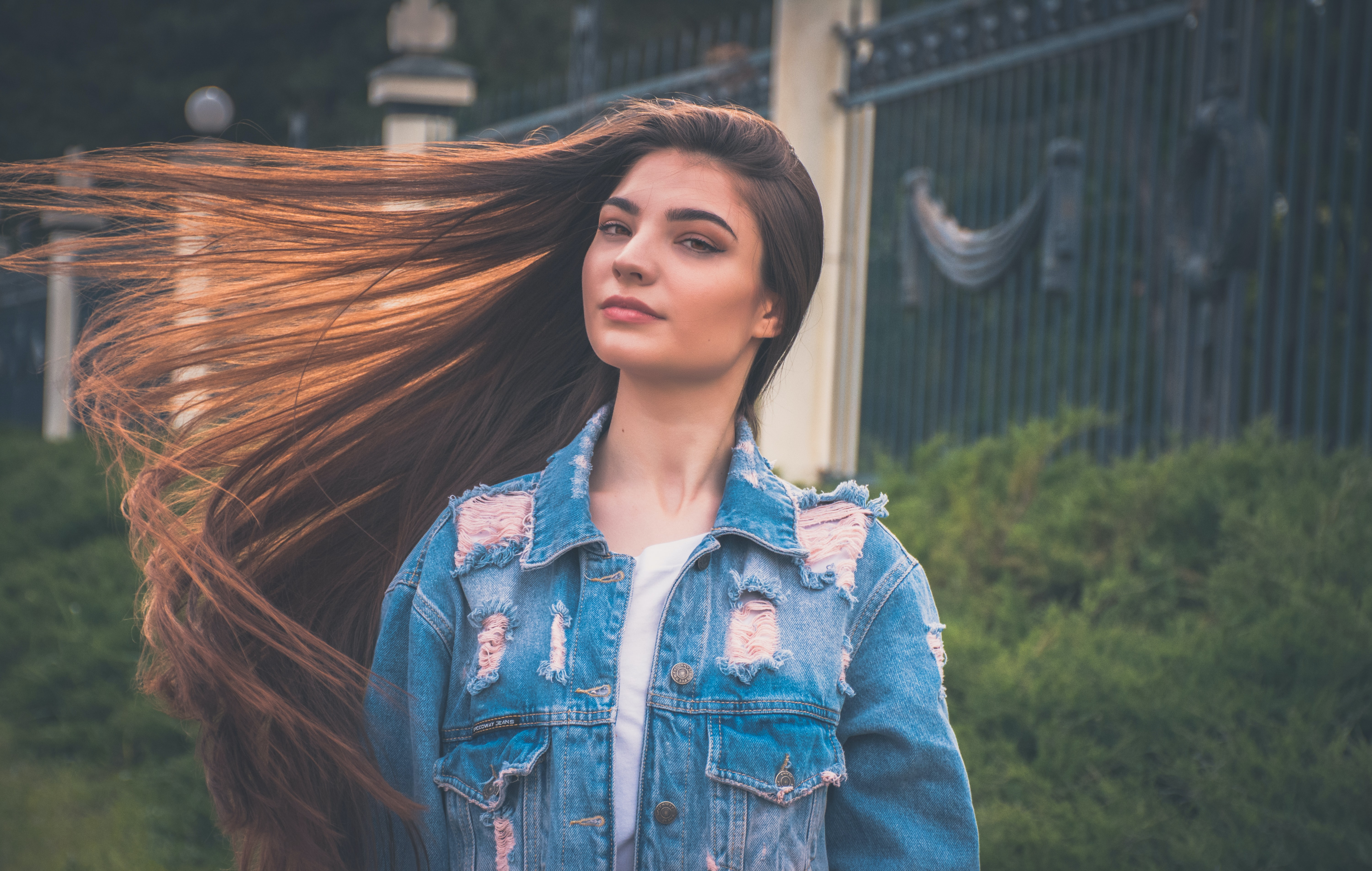 A smiling woman in a distressed denim jacket whips around her long brown hair outdoors