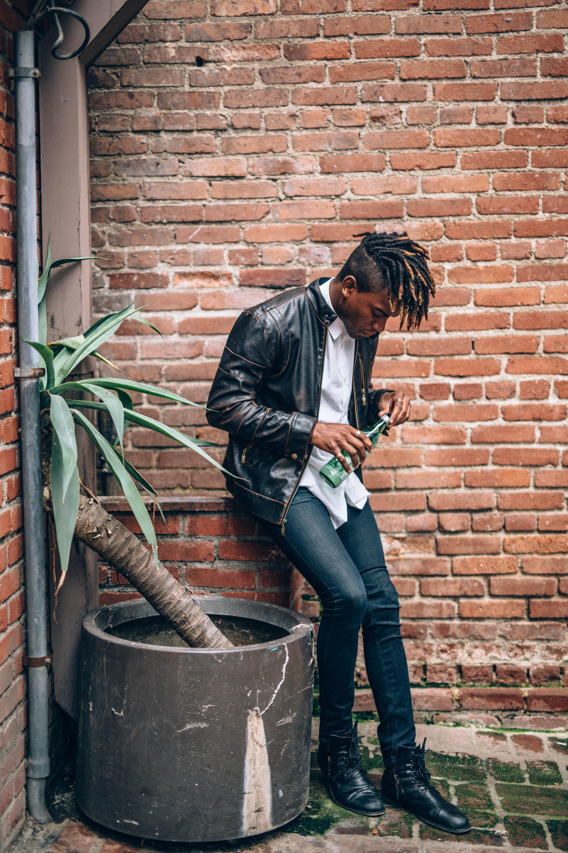 man holding green bottle near brown concrete wall