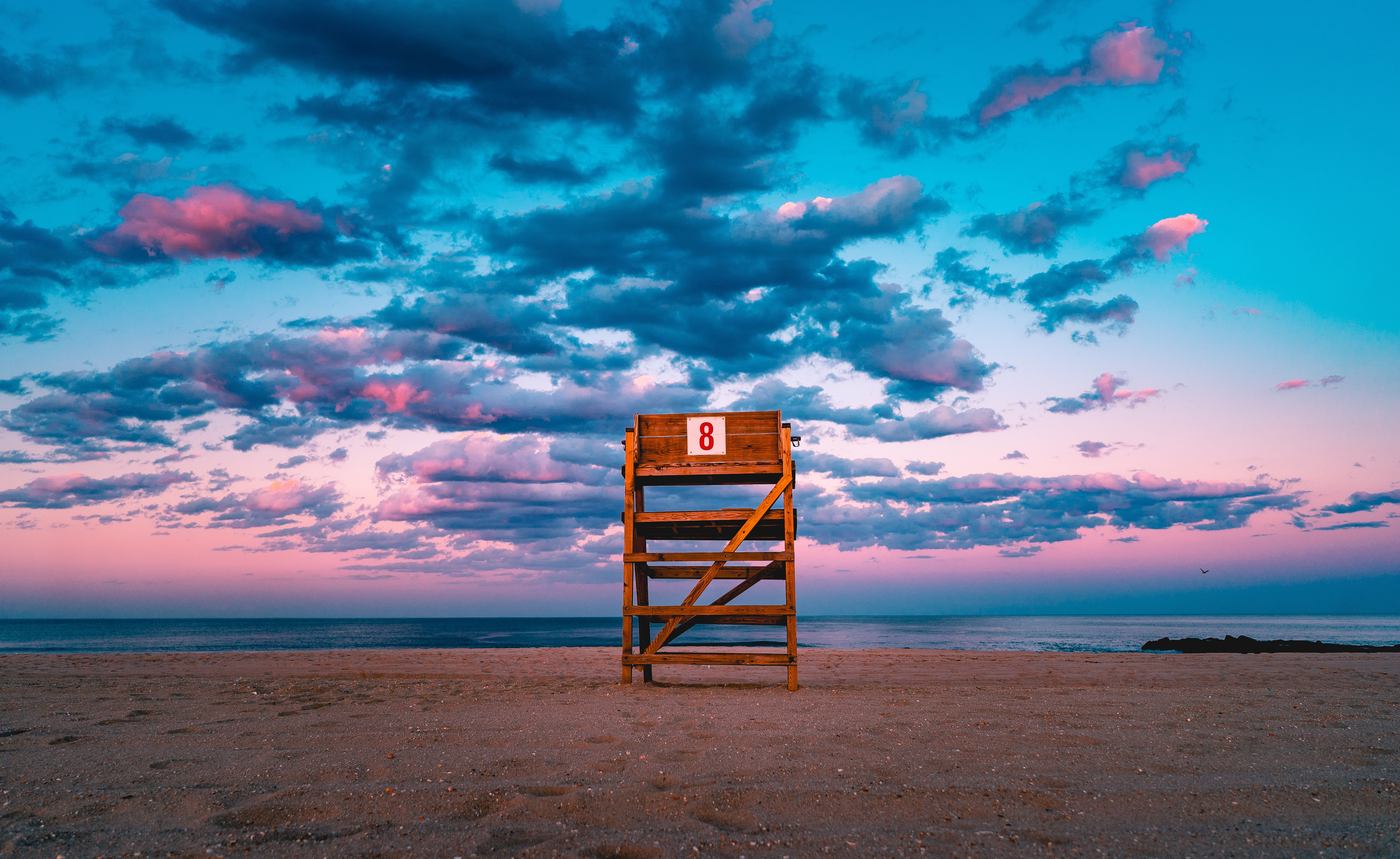 brown wooden stand on shore under gray sky