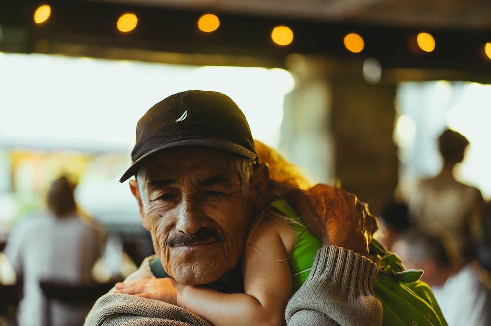 man wearing cap carrying girl inside cafe