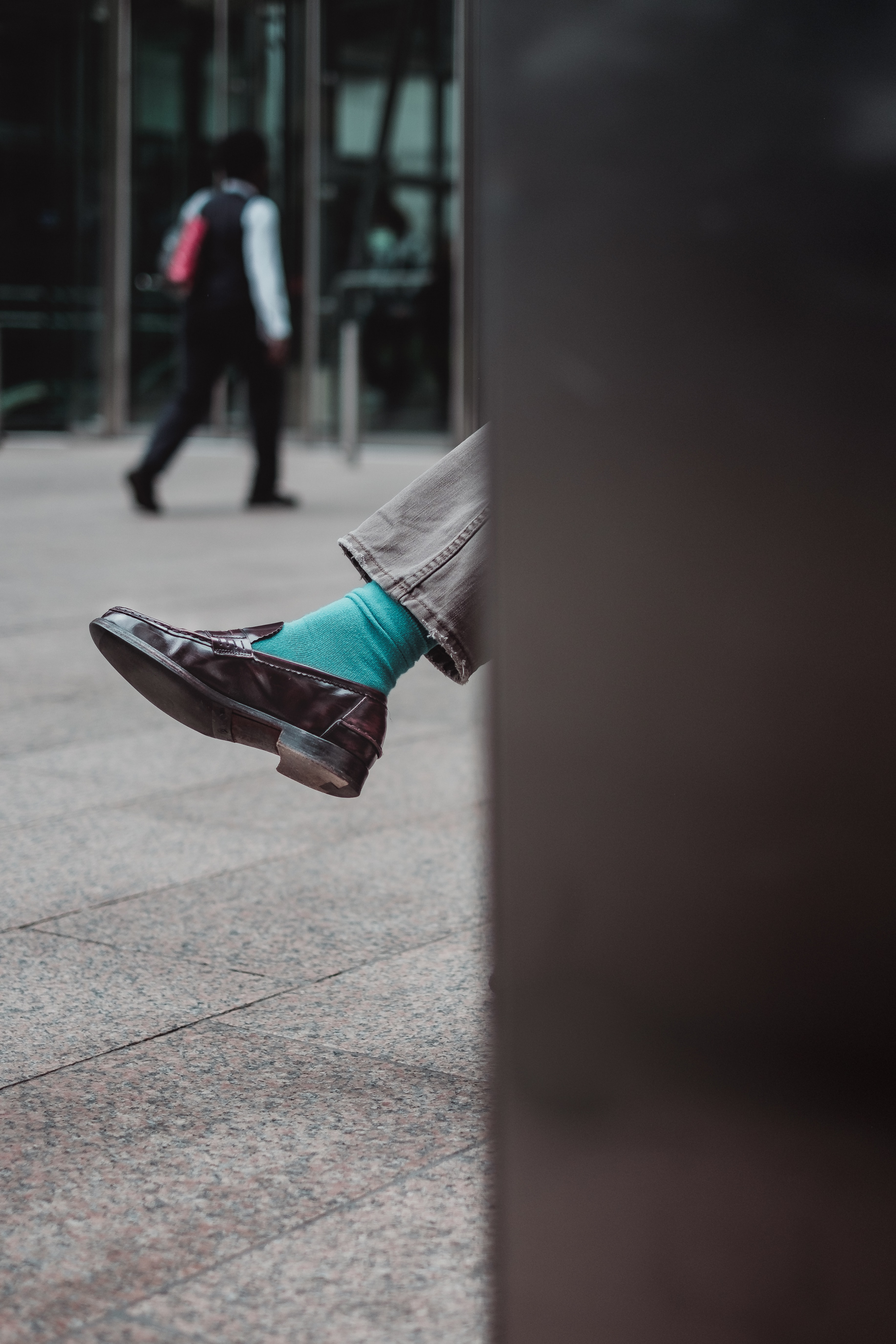 person showing unpaired brown leather dress shoe