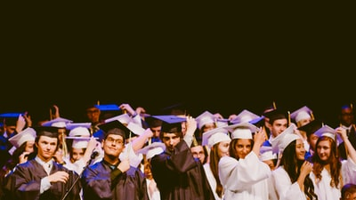 men and women wearing black and white graduation dress and mortar cap inside building diploma teams background