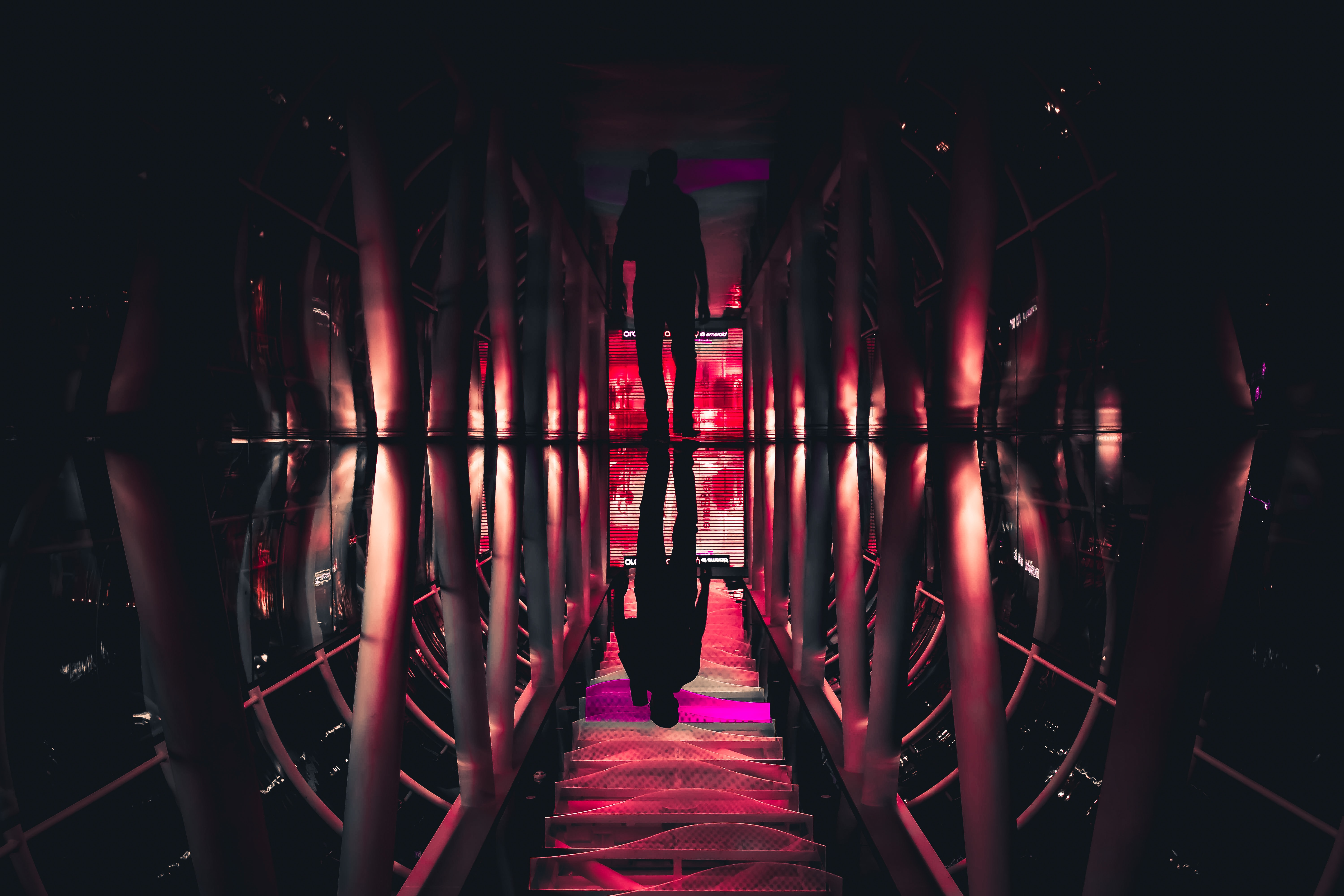 Silhouette of person walking in a dark room with glowing red lights