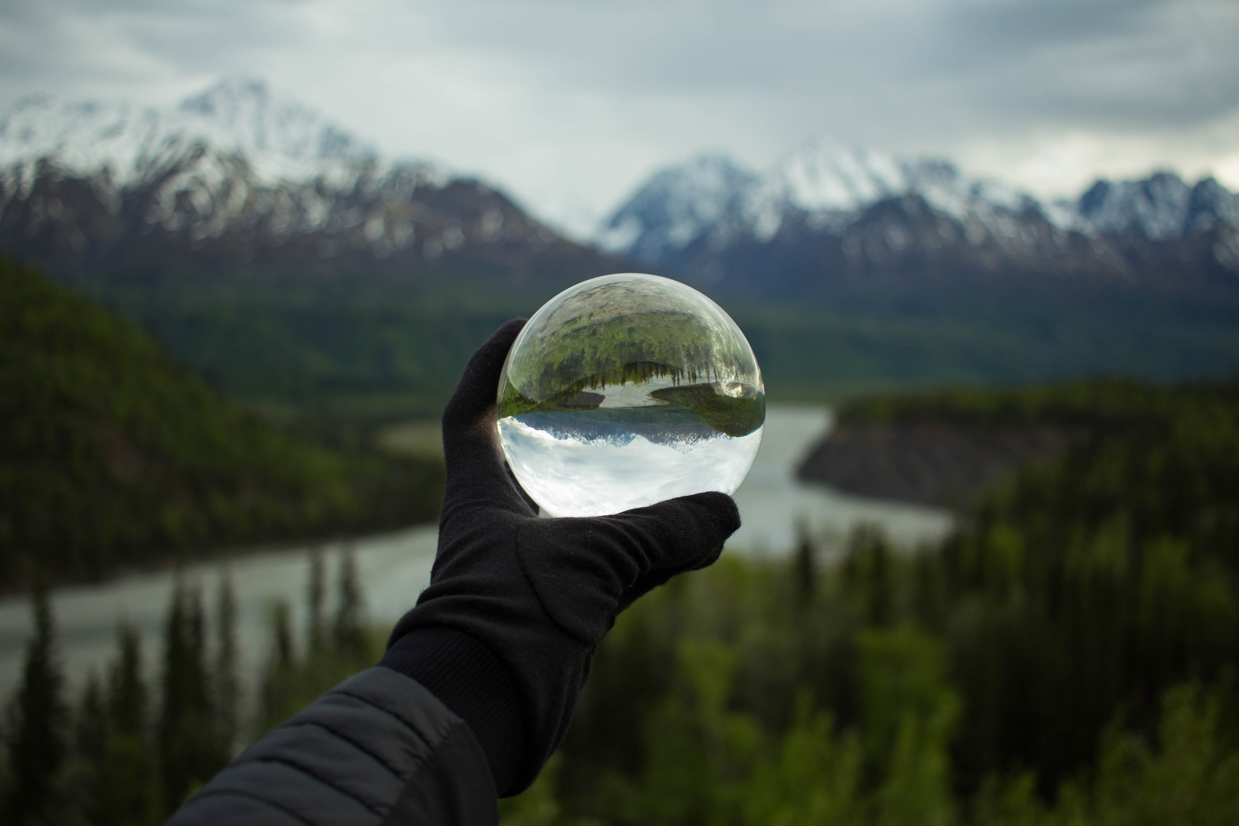 A person's hand in a glove holding a large glass ball against the backdrop of snowy mountains