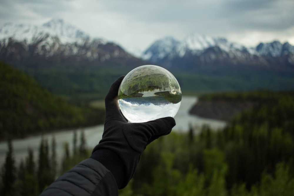 person holding glass globe