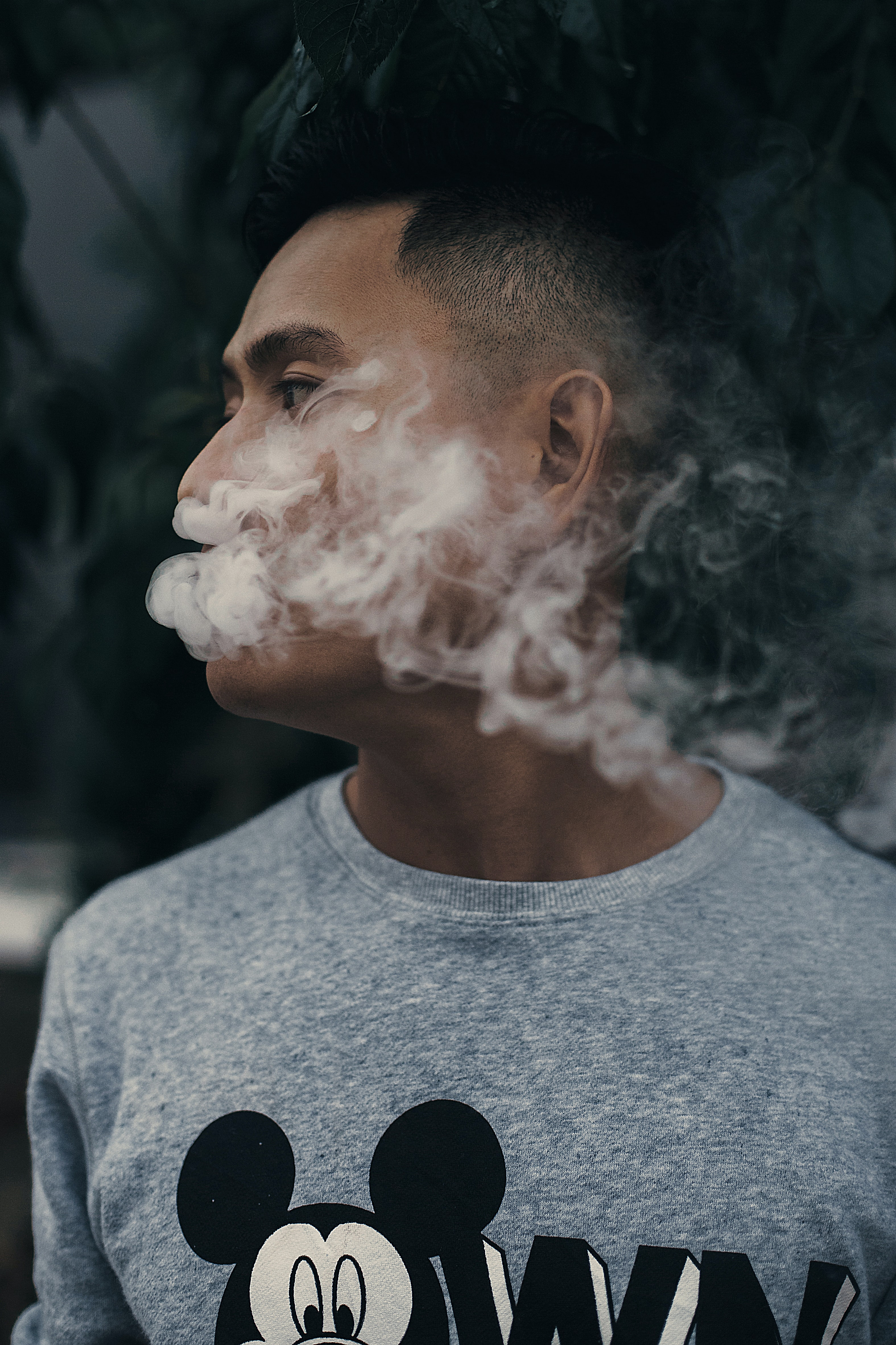Man in a mickey mouse disney sweater exhales smoke