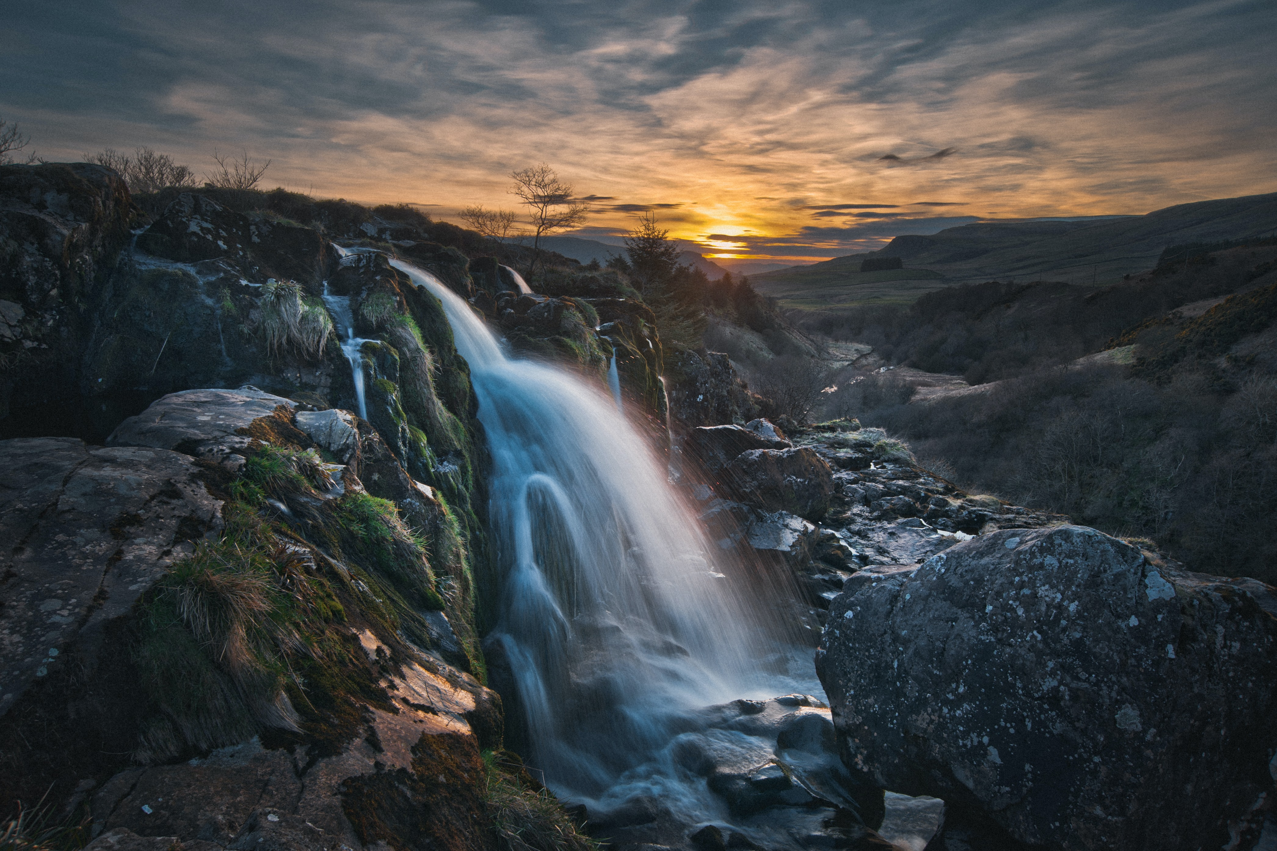 Waterfall off mossy rocks against sunset
