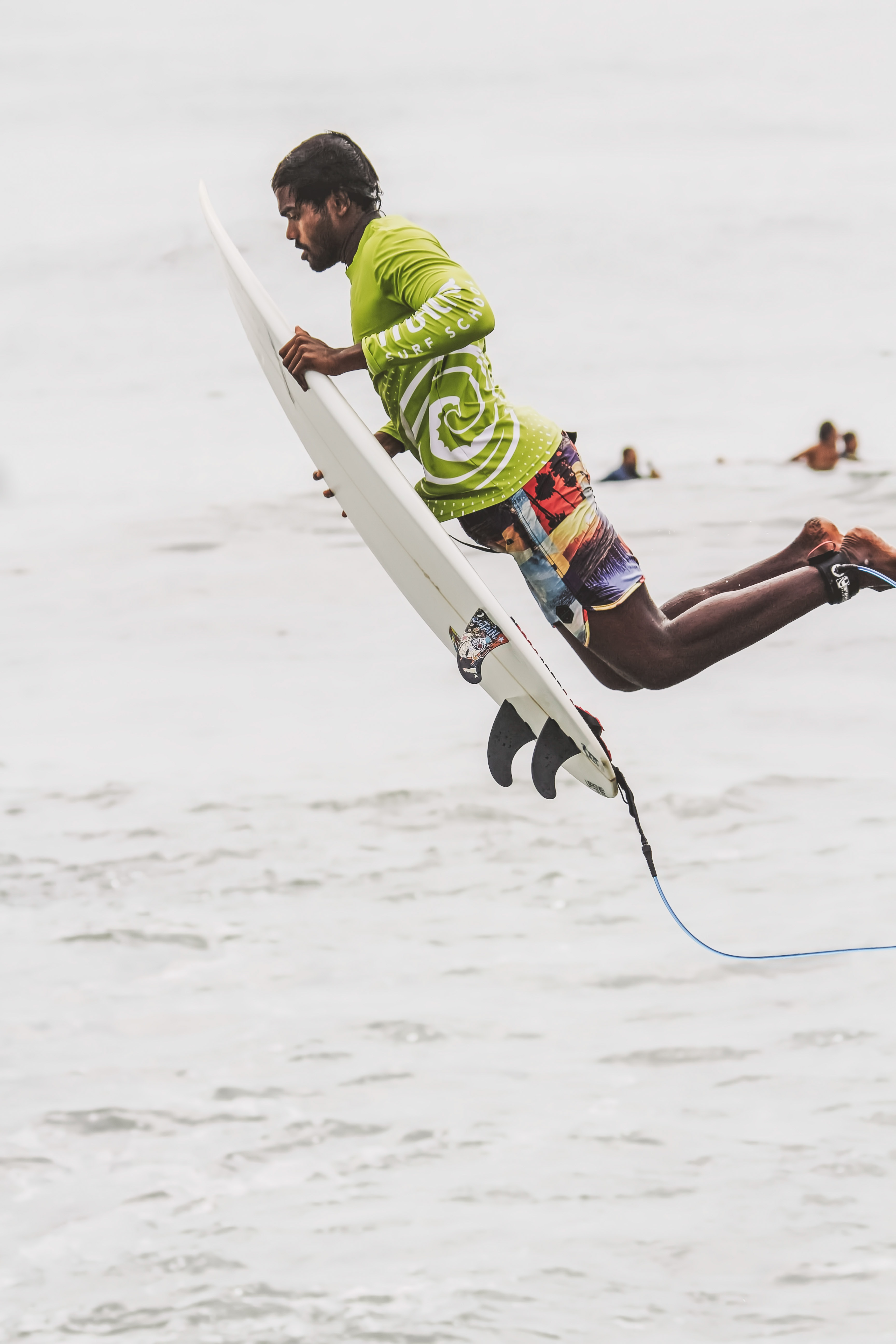 Surfer with a surfboard in mid-air after a jump at North Beach