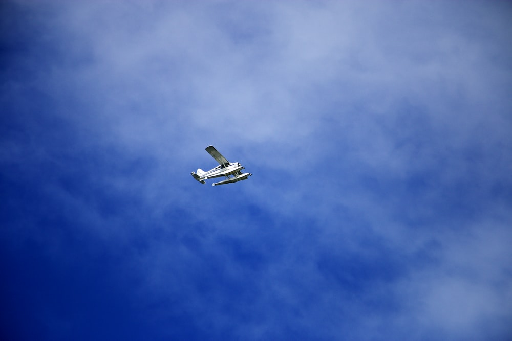 white flying biplane during white and blue sky