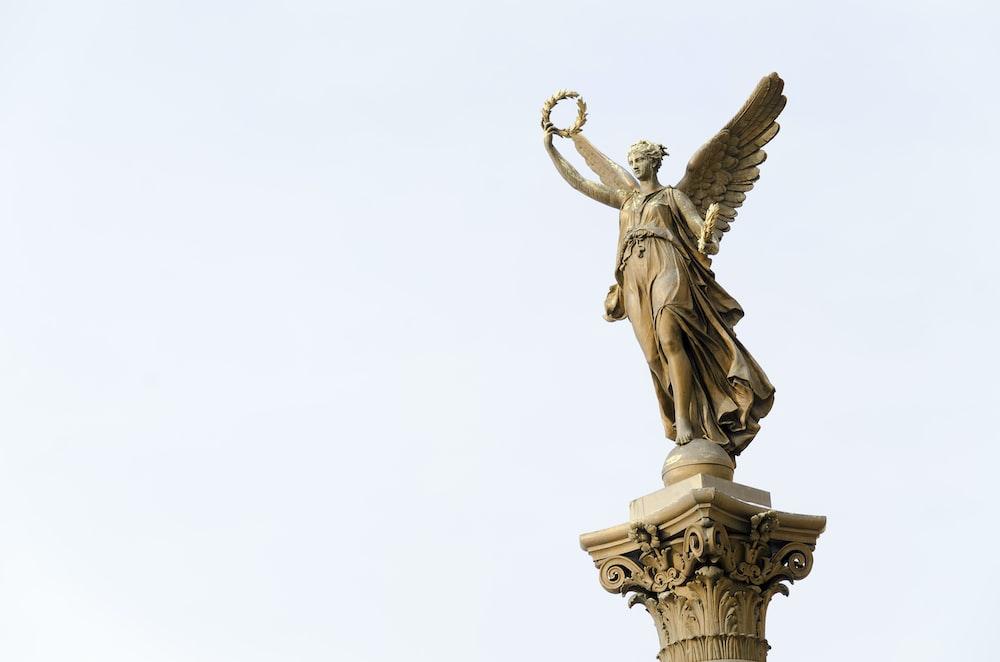 angel holding round wreath statue]