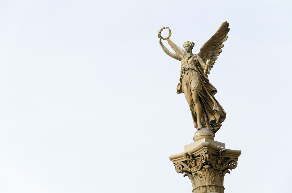angel holding round wreath statue]