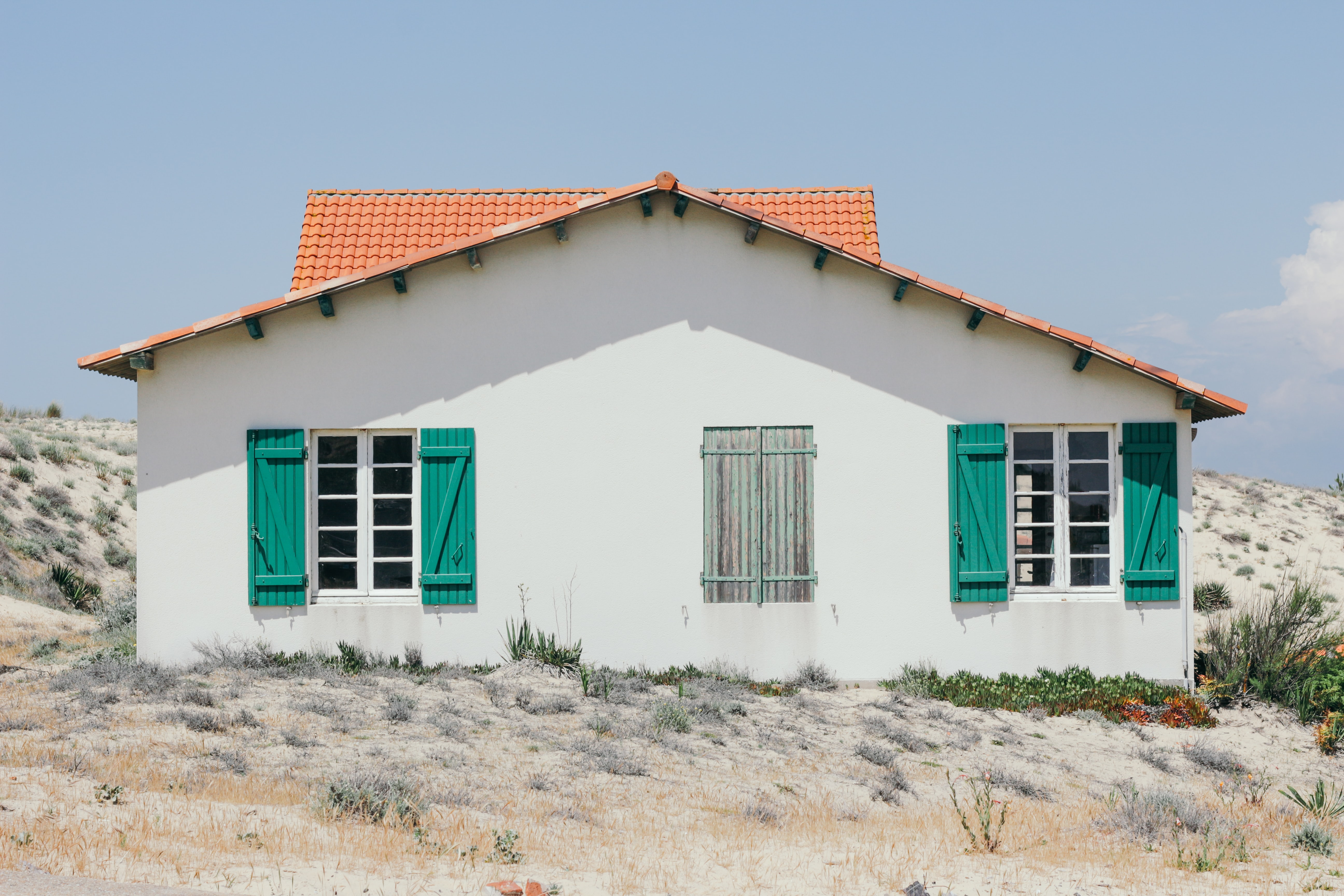 white and green concrete house with windows open at daytime