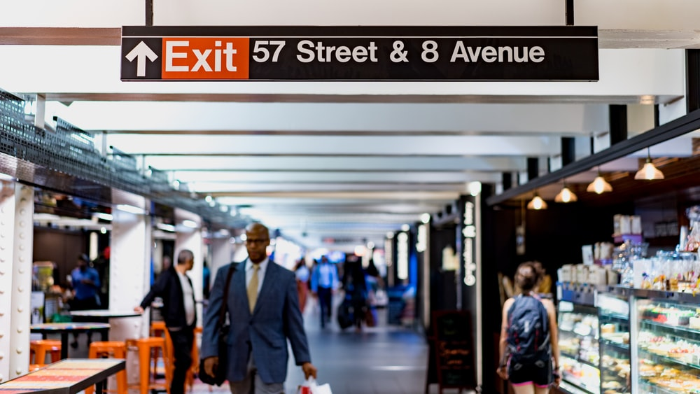 shallow focus photography of man walking under 57 Street & 8 Avenue tunnel