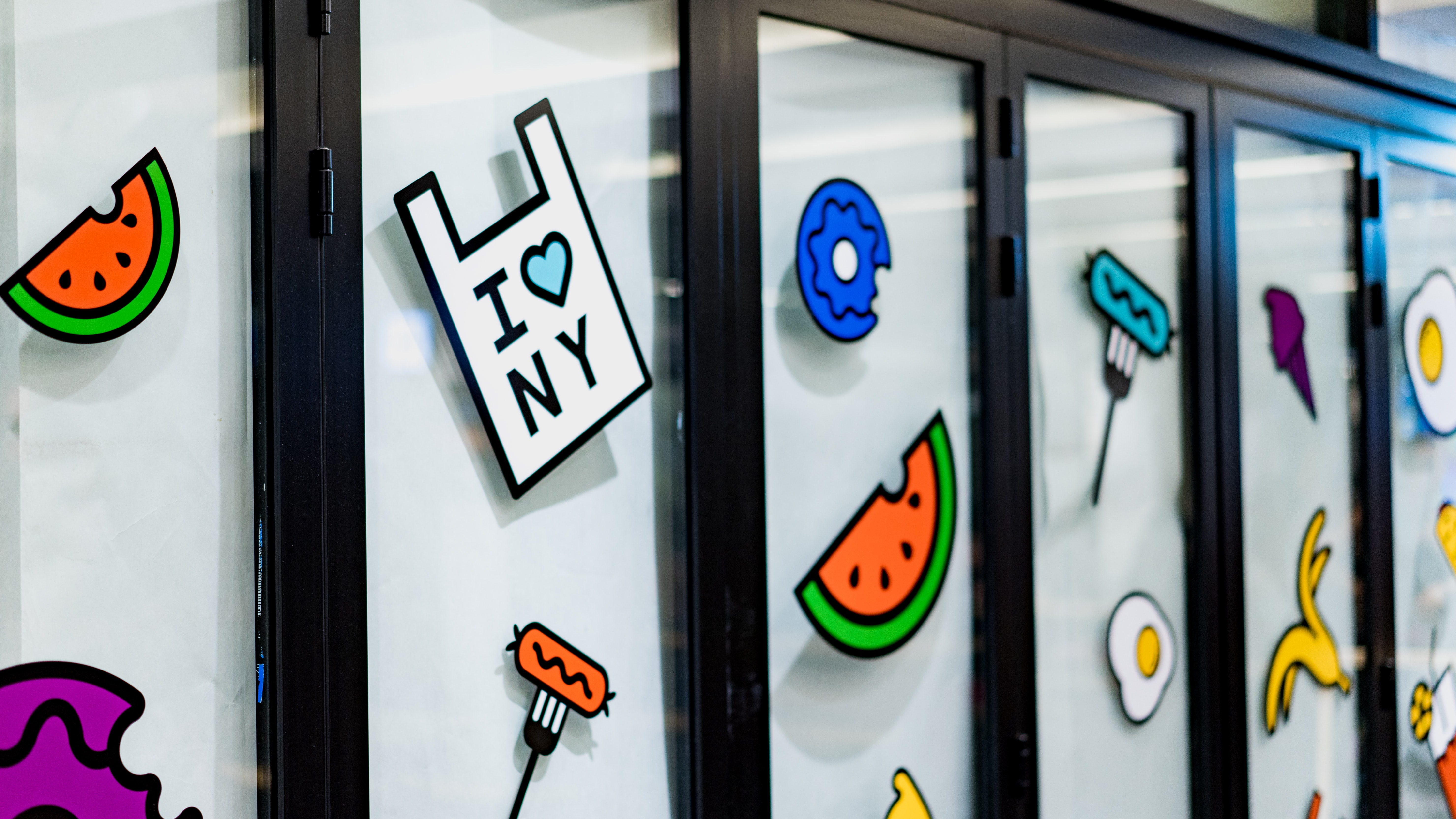 Windows with dark frames and cartoon fruit stickers in Columbus Circle