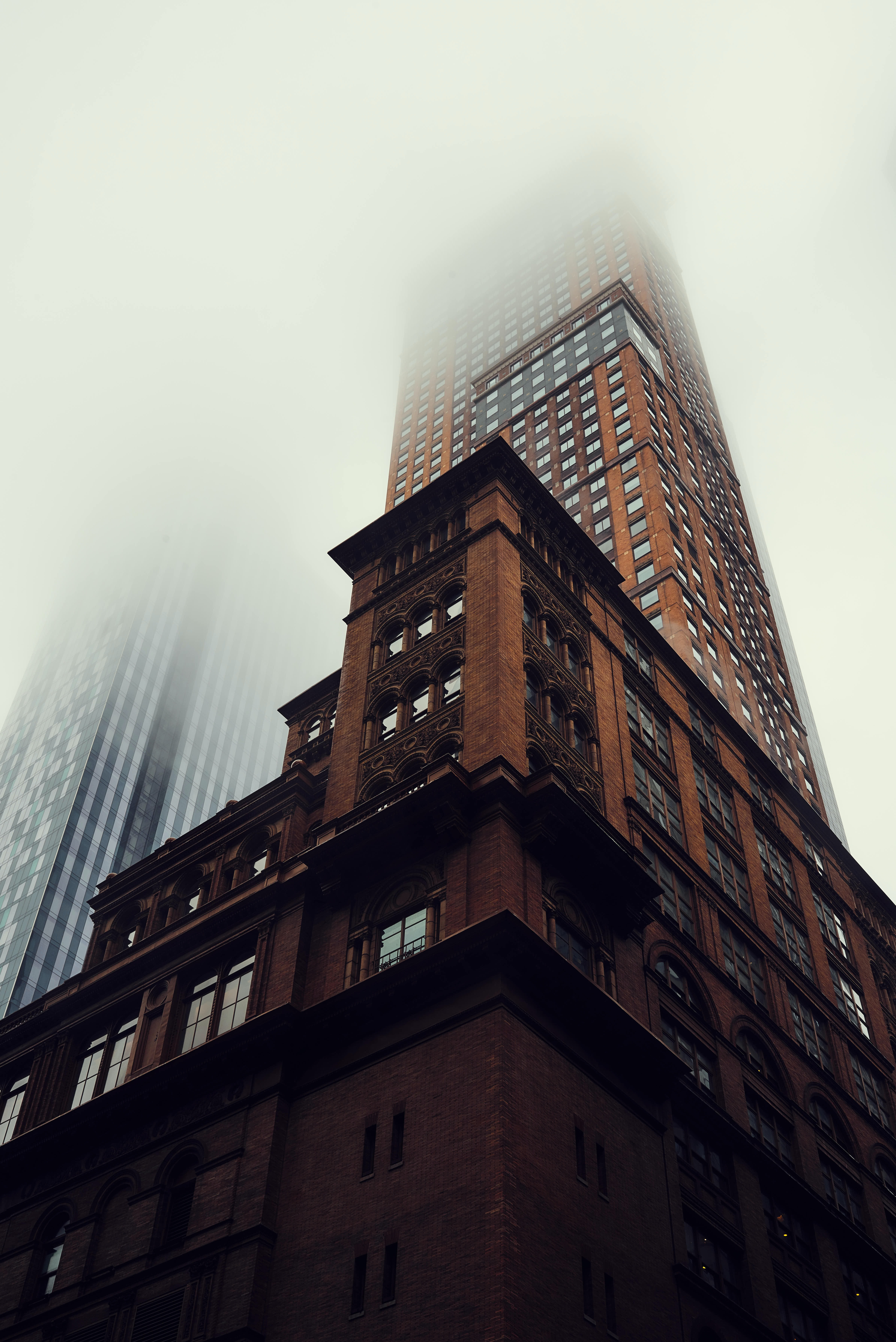 A ground view of a dark brick skyscraper disappearing into fog in New York City