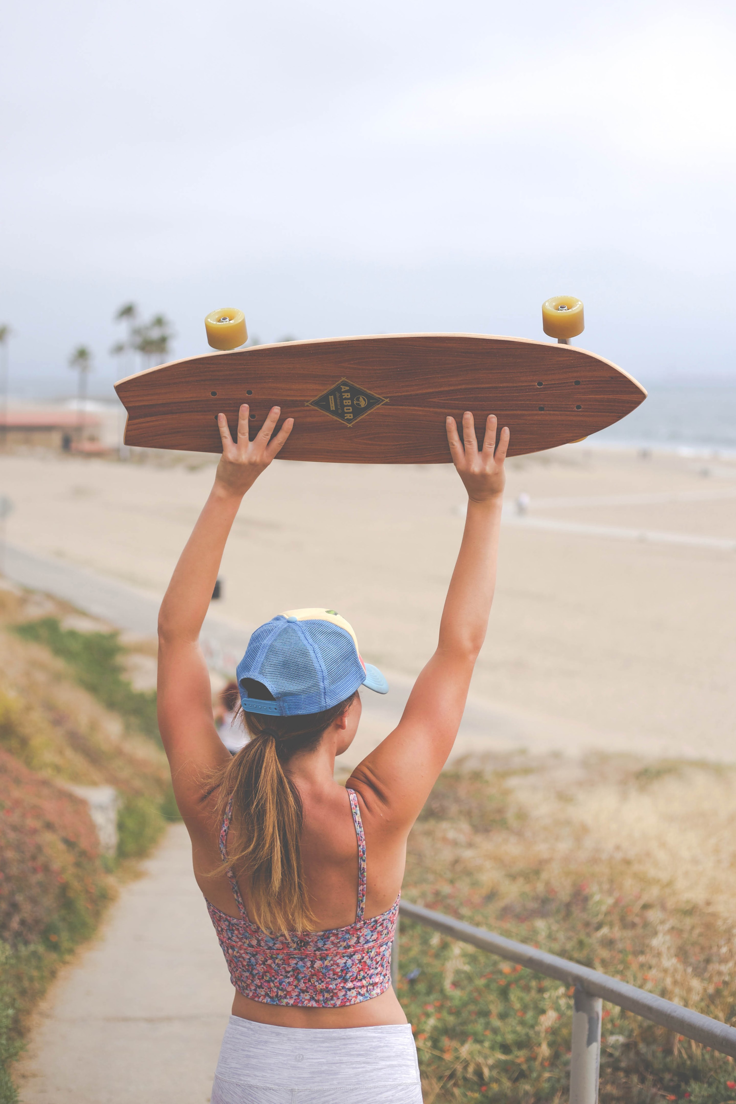 Woman holding skateboard above her head at the Playa del Rey beach