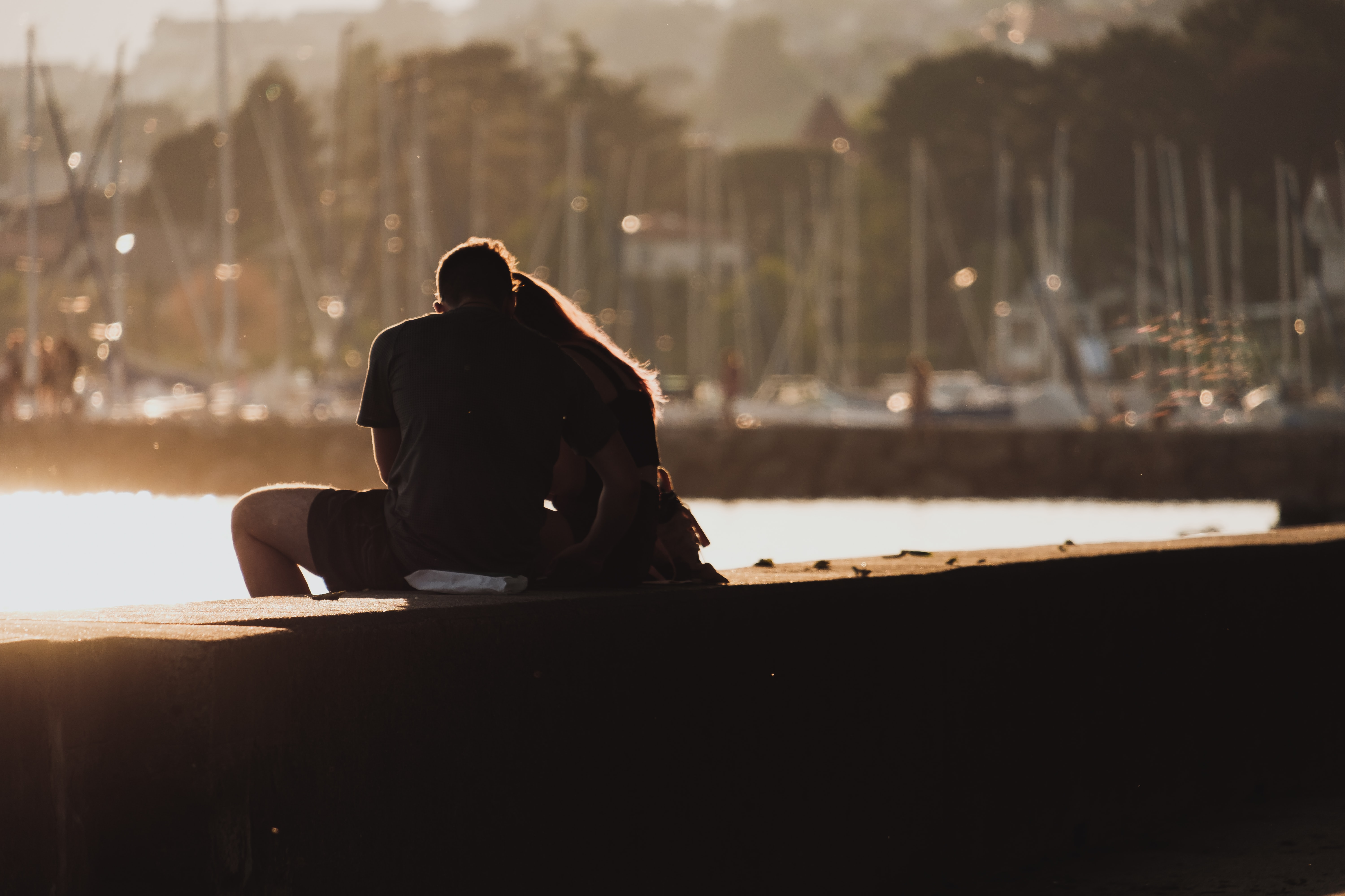 A couple sit on the harbour wall in Quai Gustave Doret, with boats in the background as the sun sets at dusk.