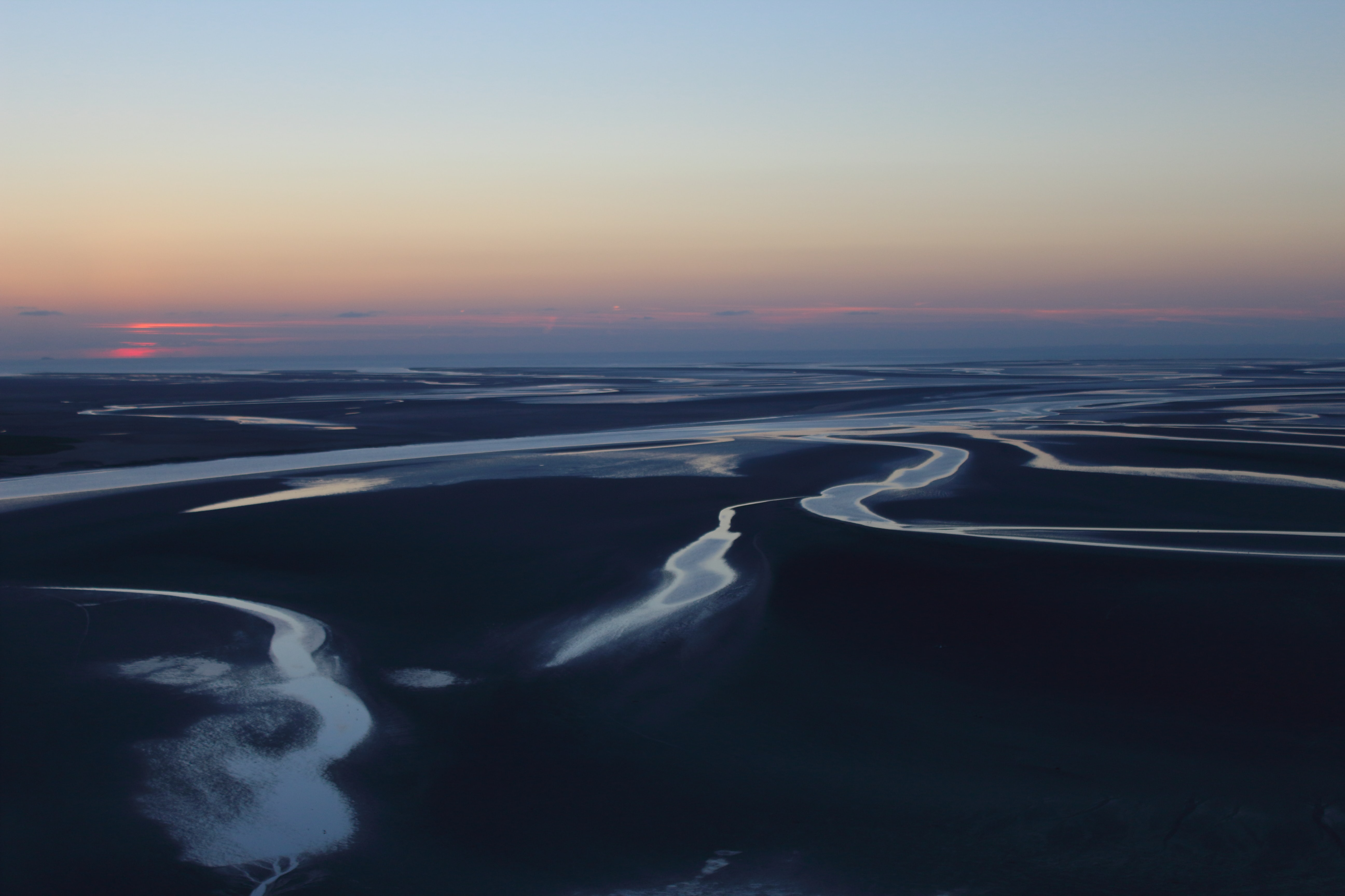 A hazy shot of the sea during the low tide at sunset