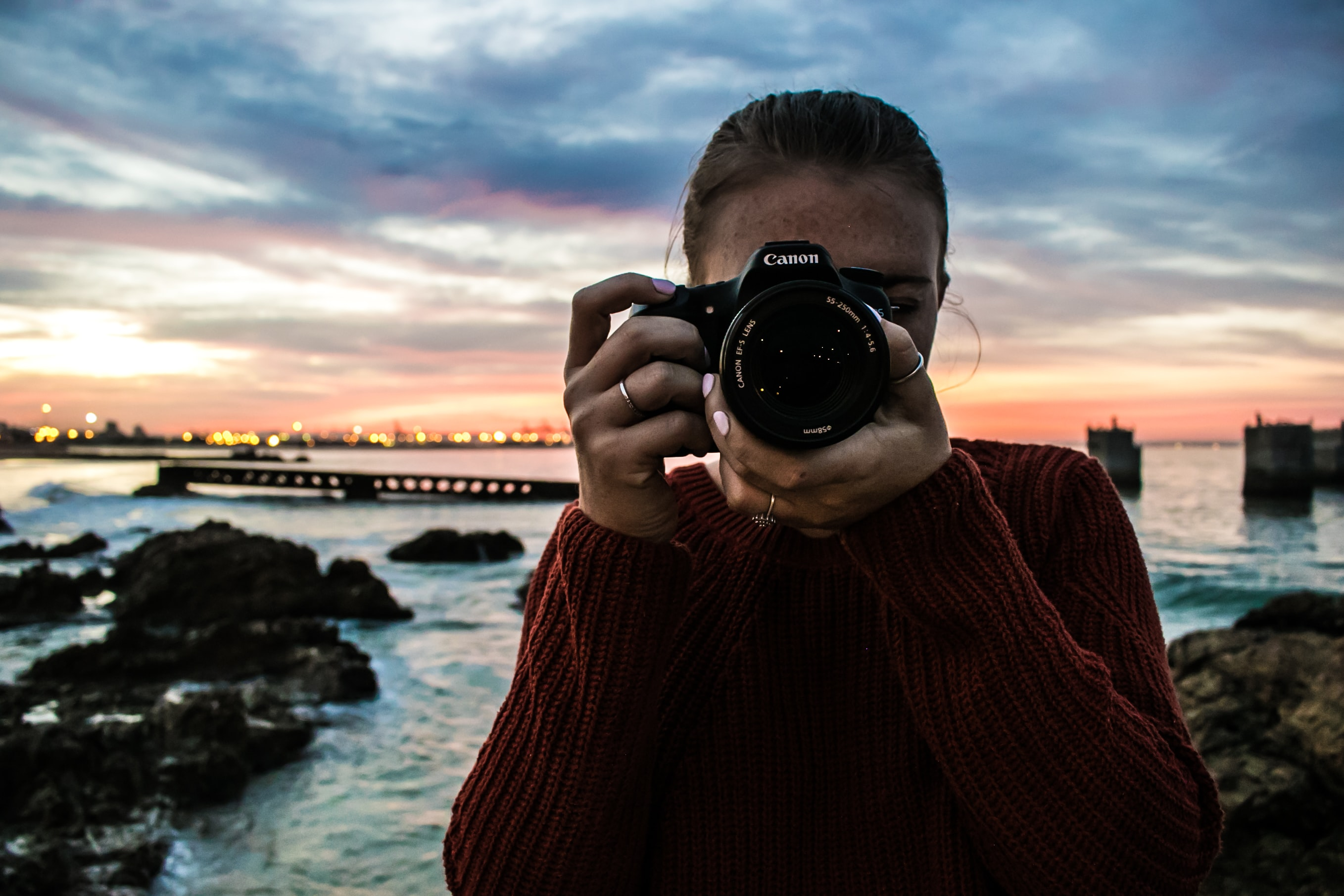 Female photographer with a Canon camera at the rocky seashore of Port Elizabeth during sunset