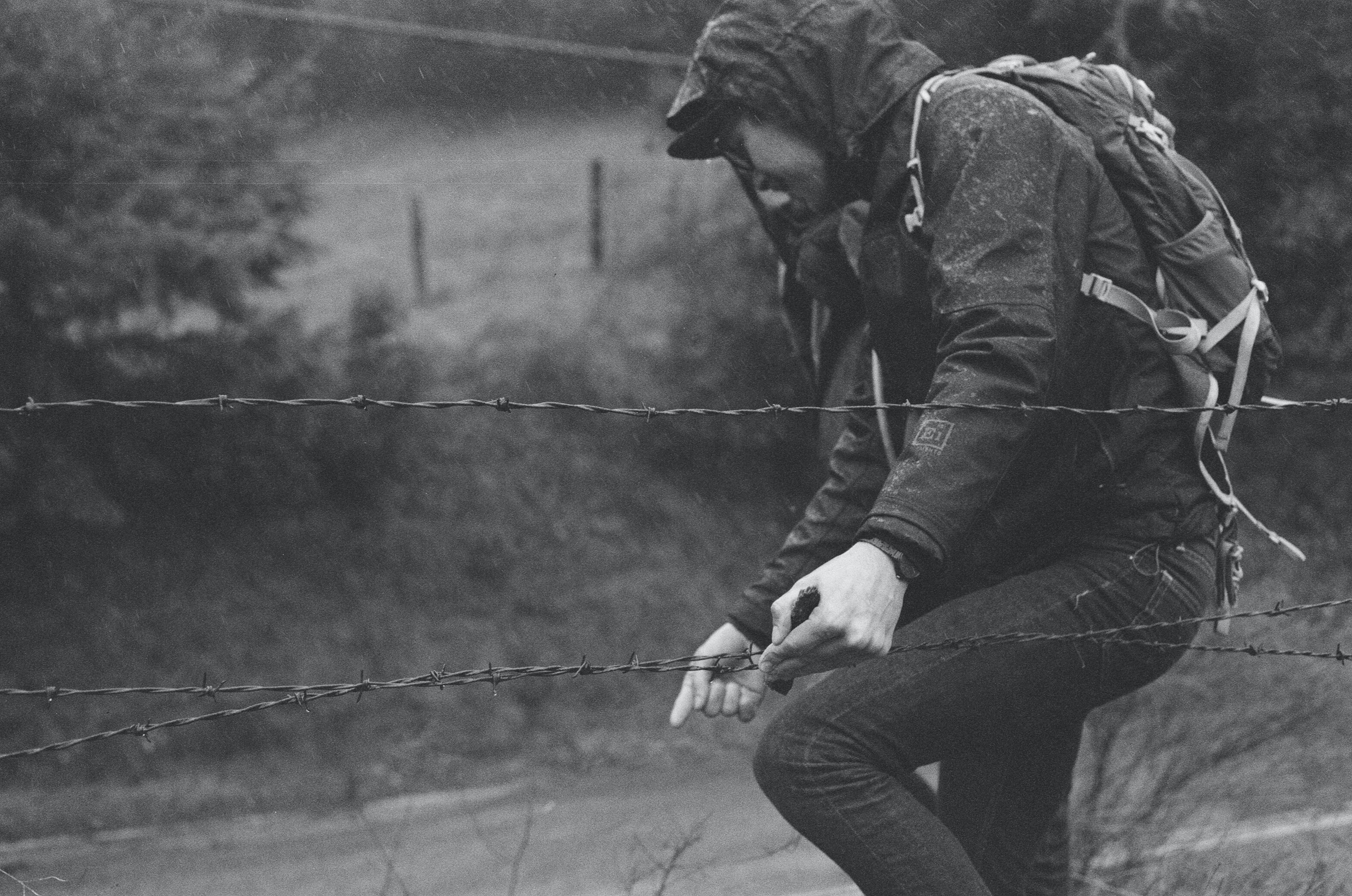 Black and white shot of person with backpack and outdoor clothing climbing through barbed wire fence