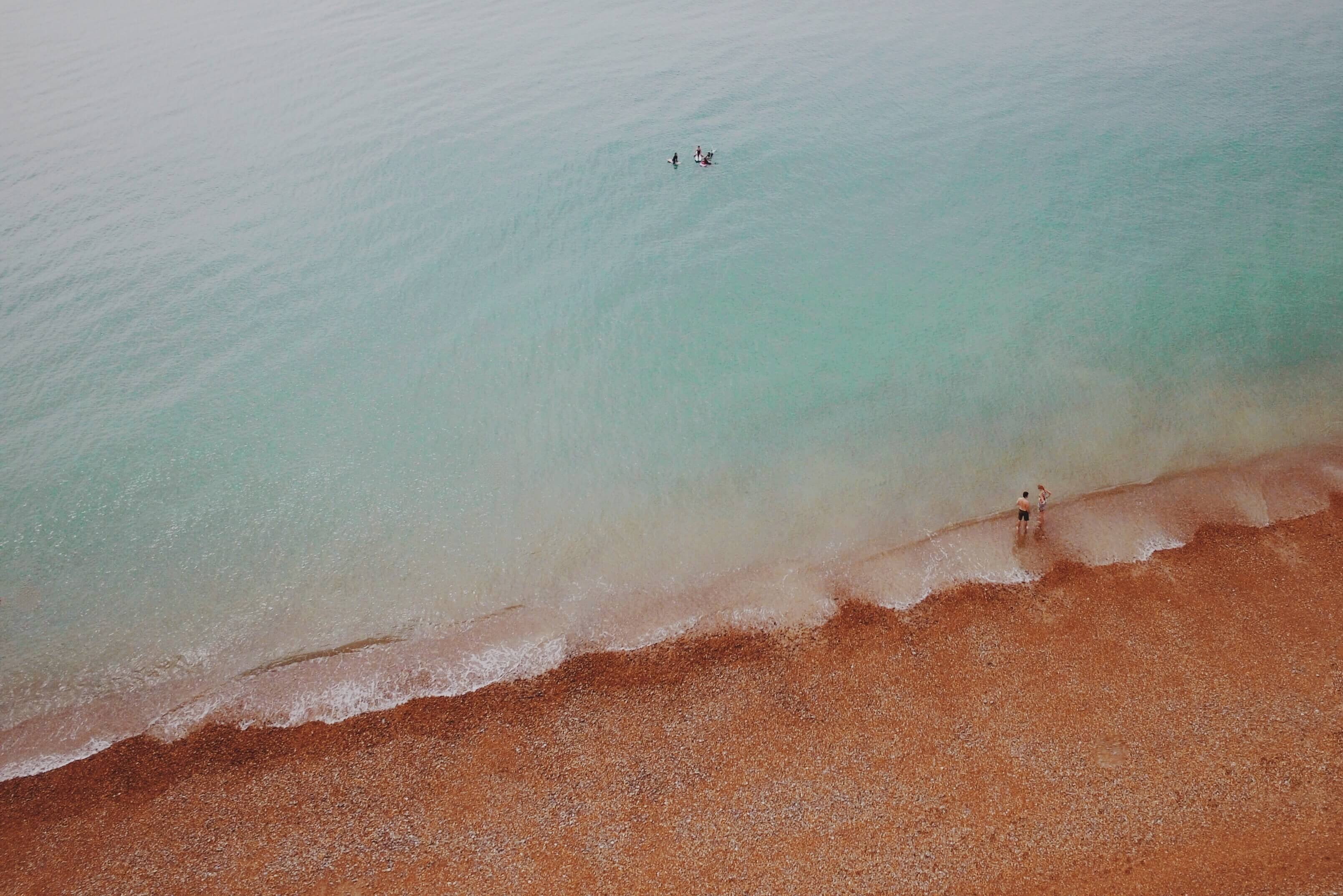 Drone view of people swimming in clear ocean washing up on red sand beach in Brighton