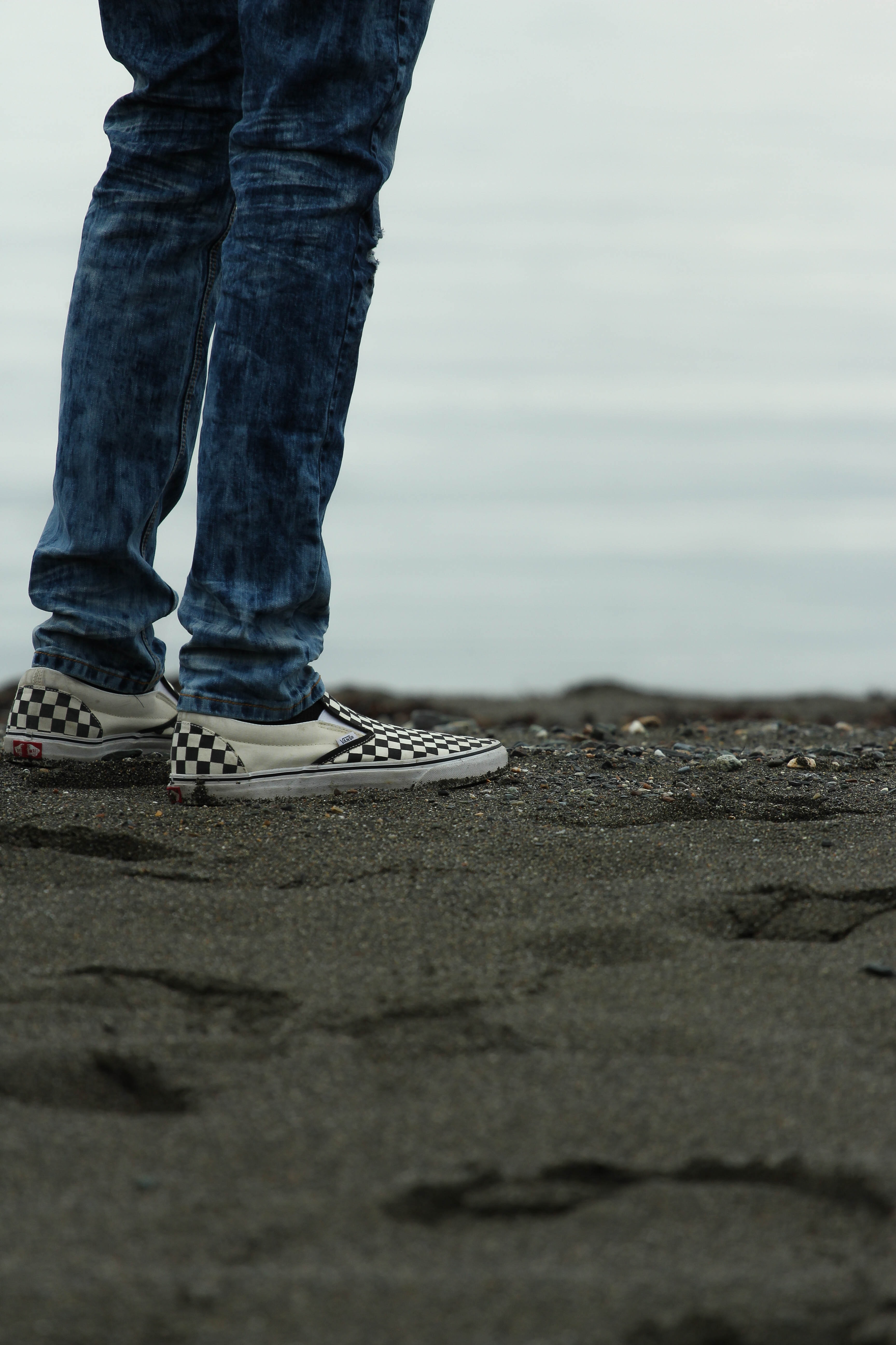 Man in jeans and canvas loafers standing on a black sand beach in Yukon