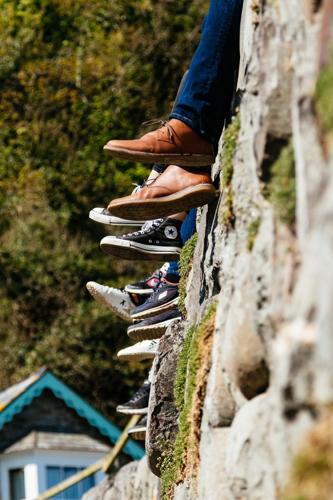 People sat on a wall - Shoes and Converse