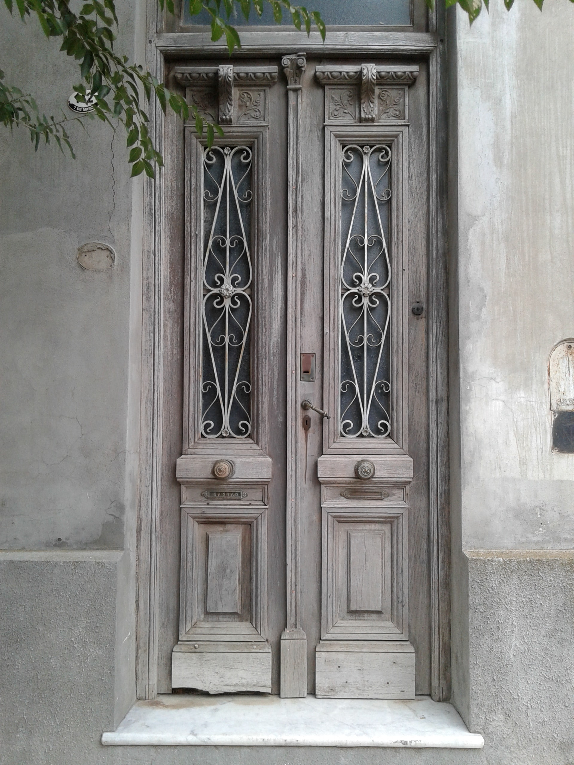 Old vintage door with light wood and tall decorative glass windows on a tan building