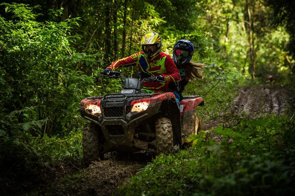 man and woman riding on ATV