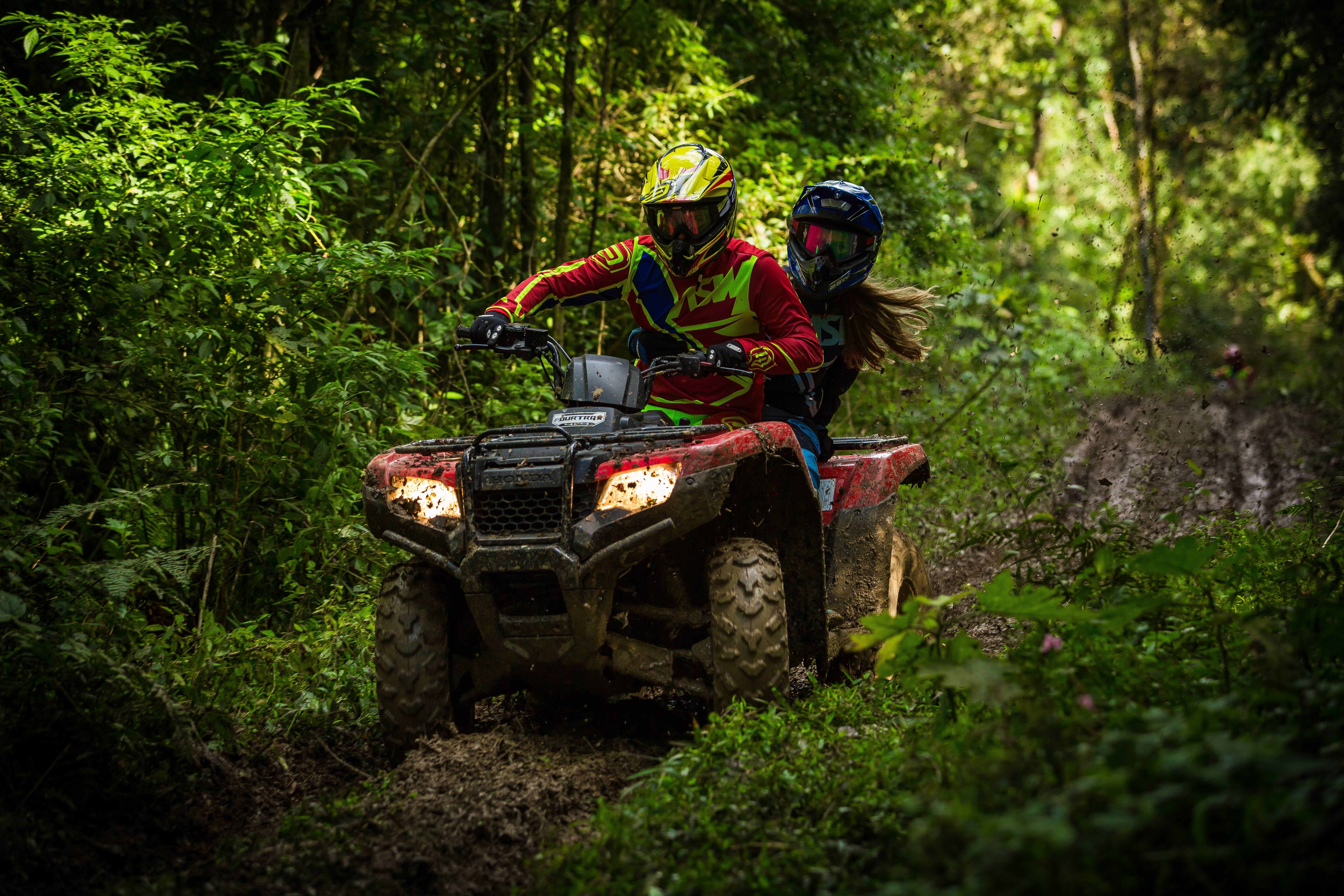 Two people driving a quad bike through a jungle in Ct Leandro Silva