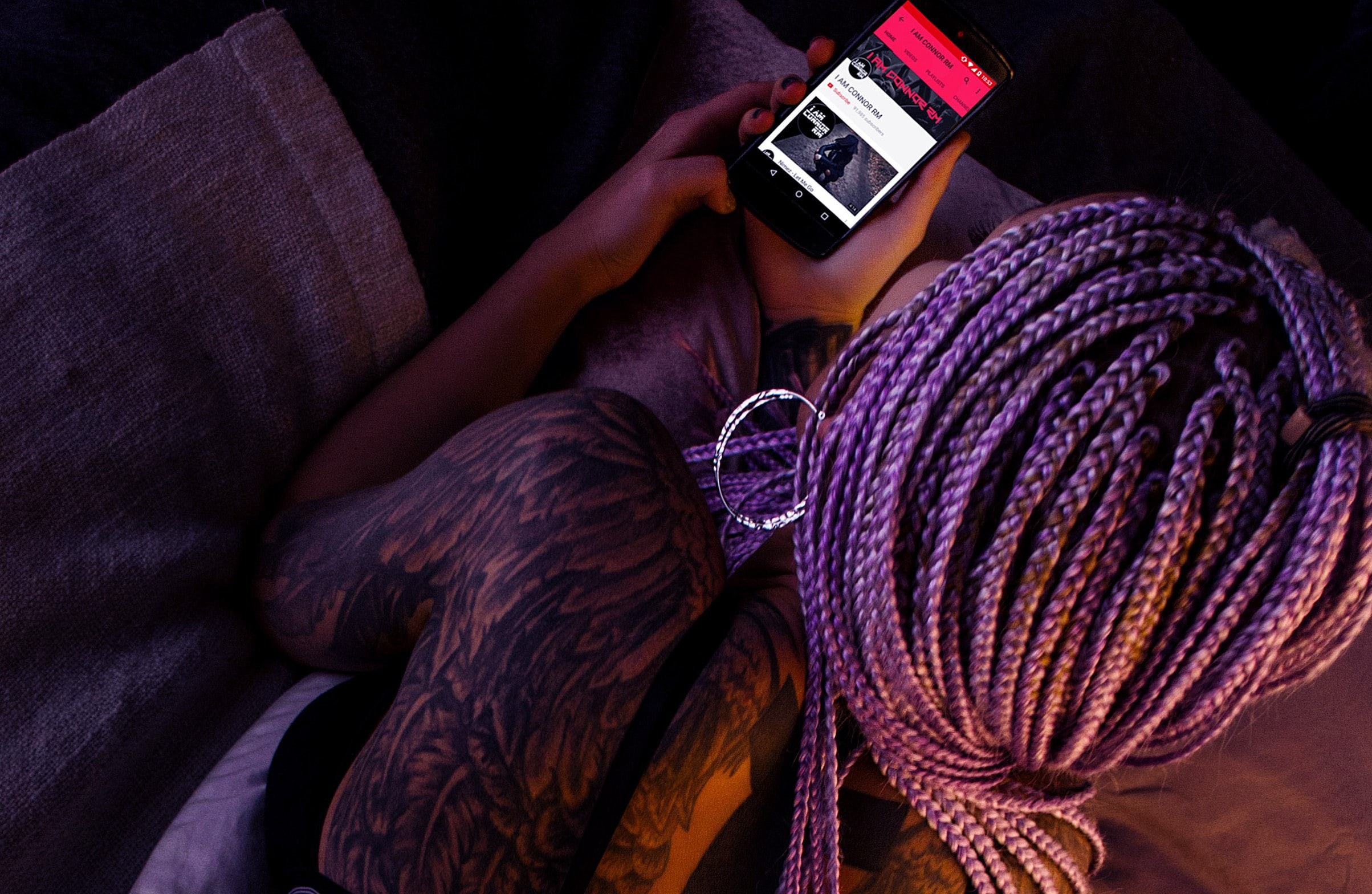 A woman in purple dreadlocks with tattoos on her back looking at a music application on a phone