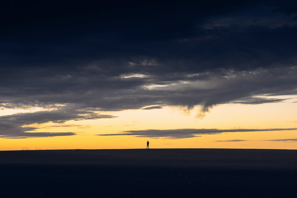 silhouette of person standing on hill during sunset