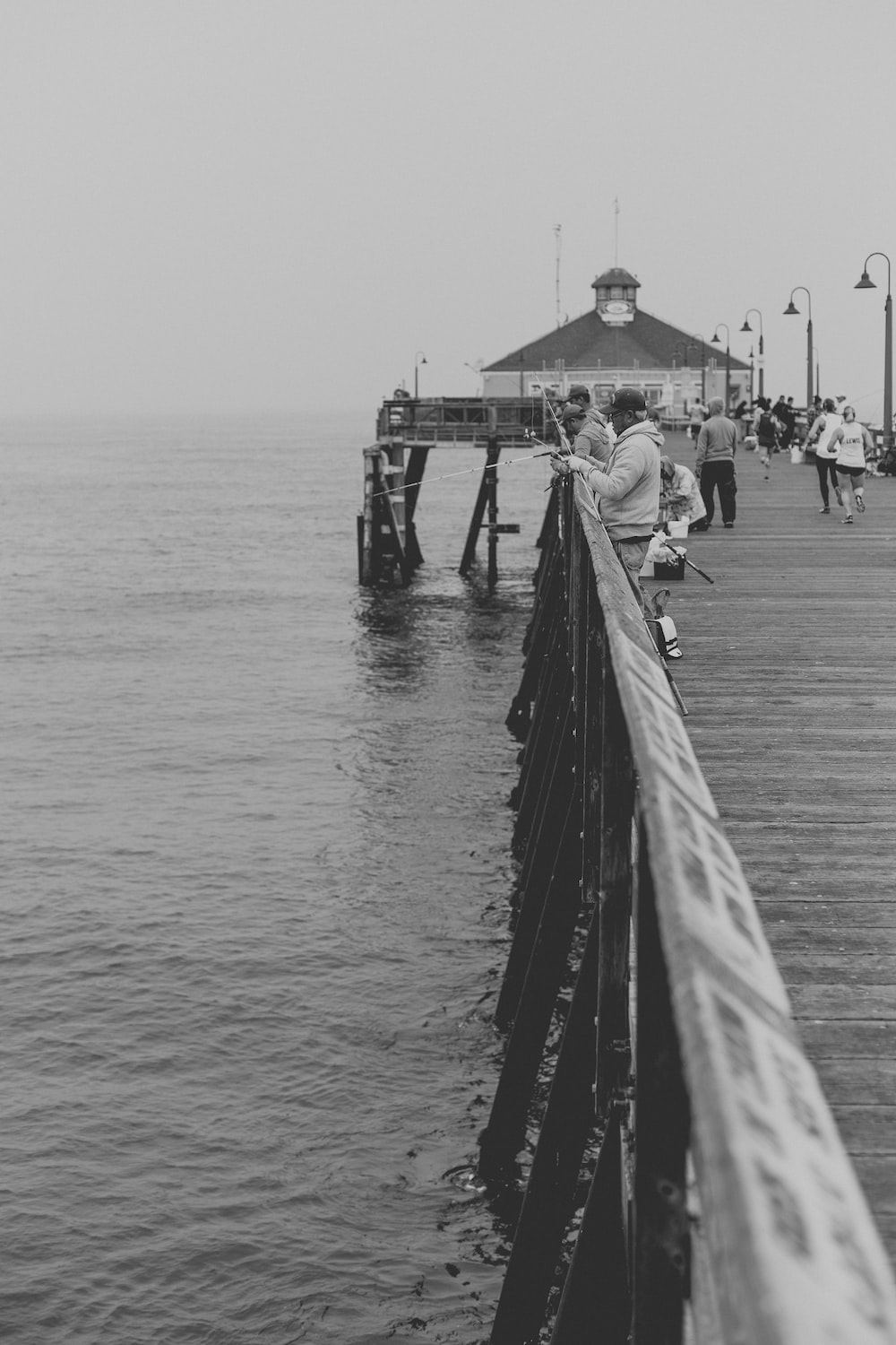 Black And White Photograph Of People Fishing On A Pier At Imperial Beach