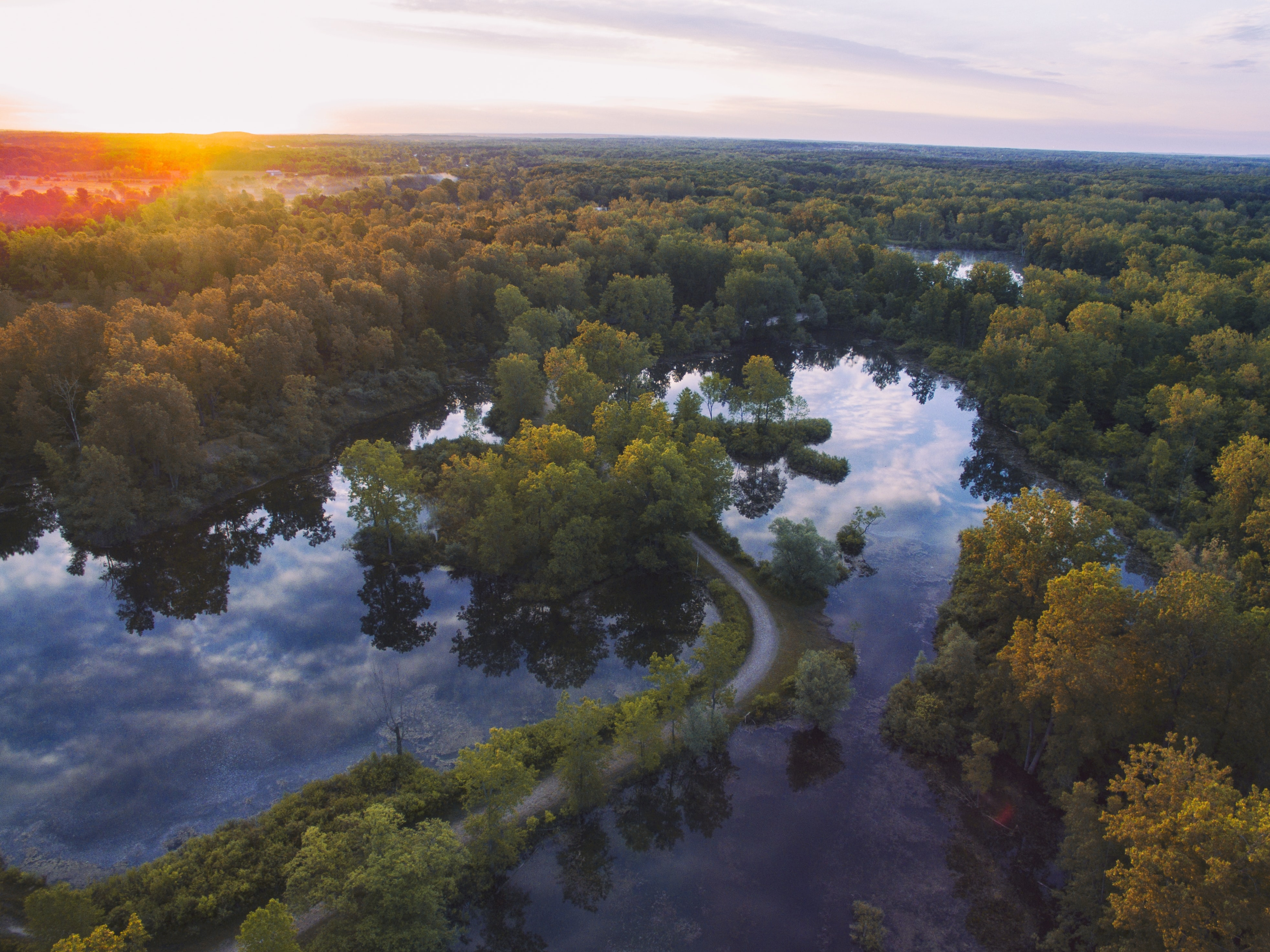 Aerial view of a road winding through the rivers of Otisville, Michigan during a golden sunset