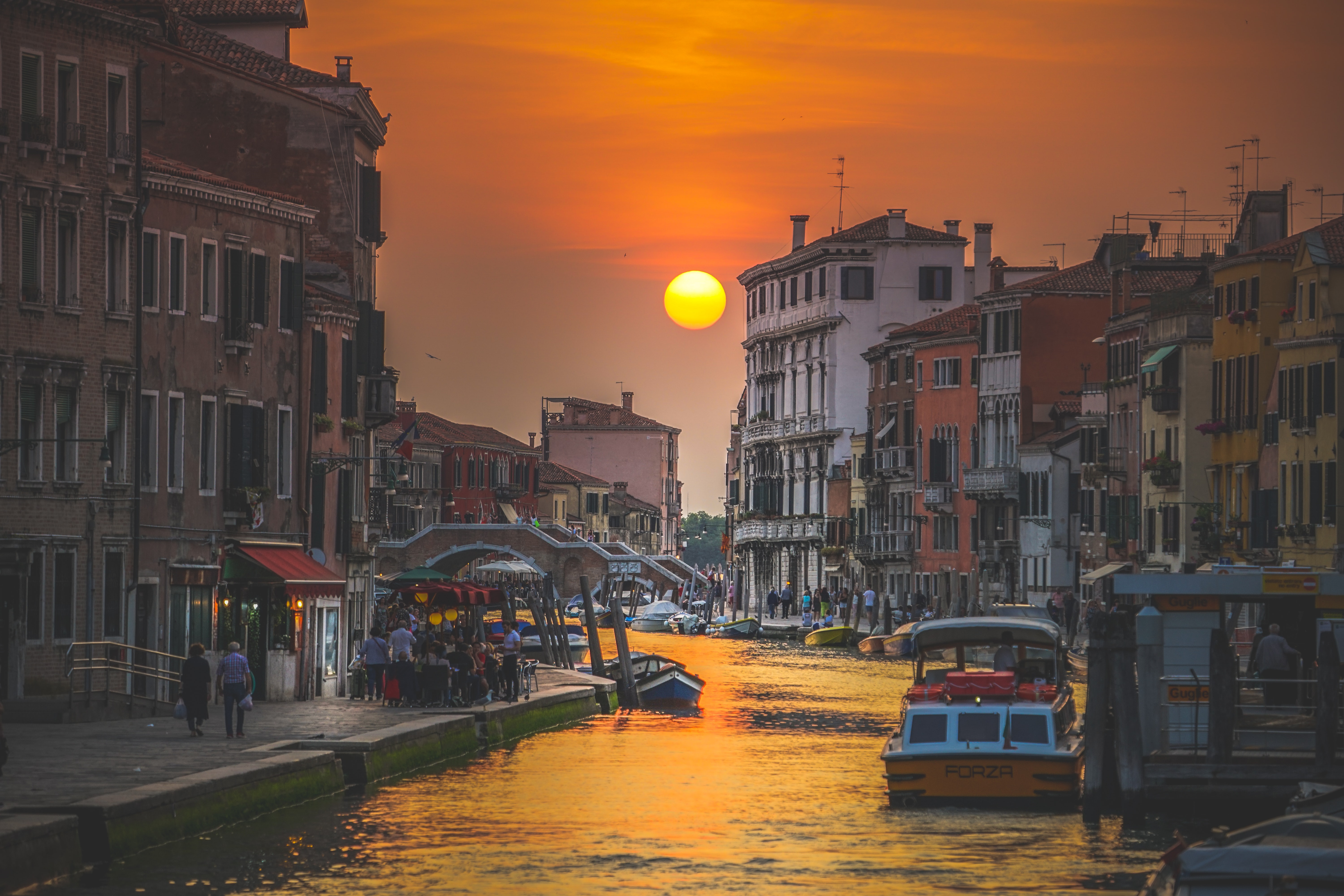 An Italian canal bathed in the warm light of the setting sun with a bridge at the back