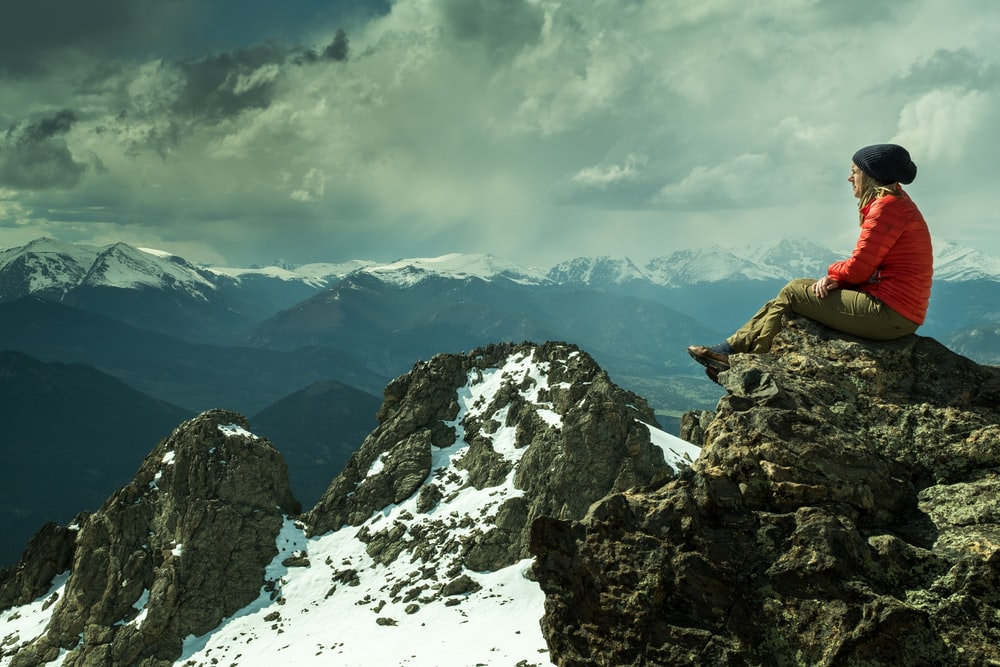 person sitting on rock across snow covered mountain under cloudy sky